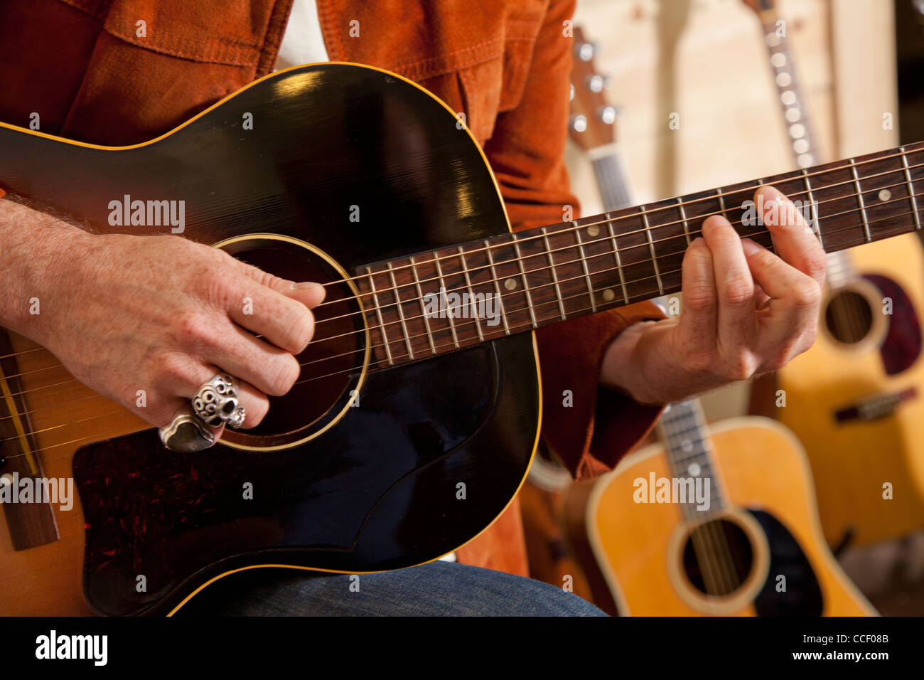 Close-up of man's torso practicing with guitar - Stock Image