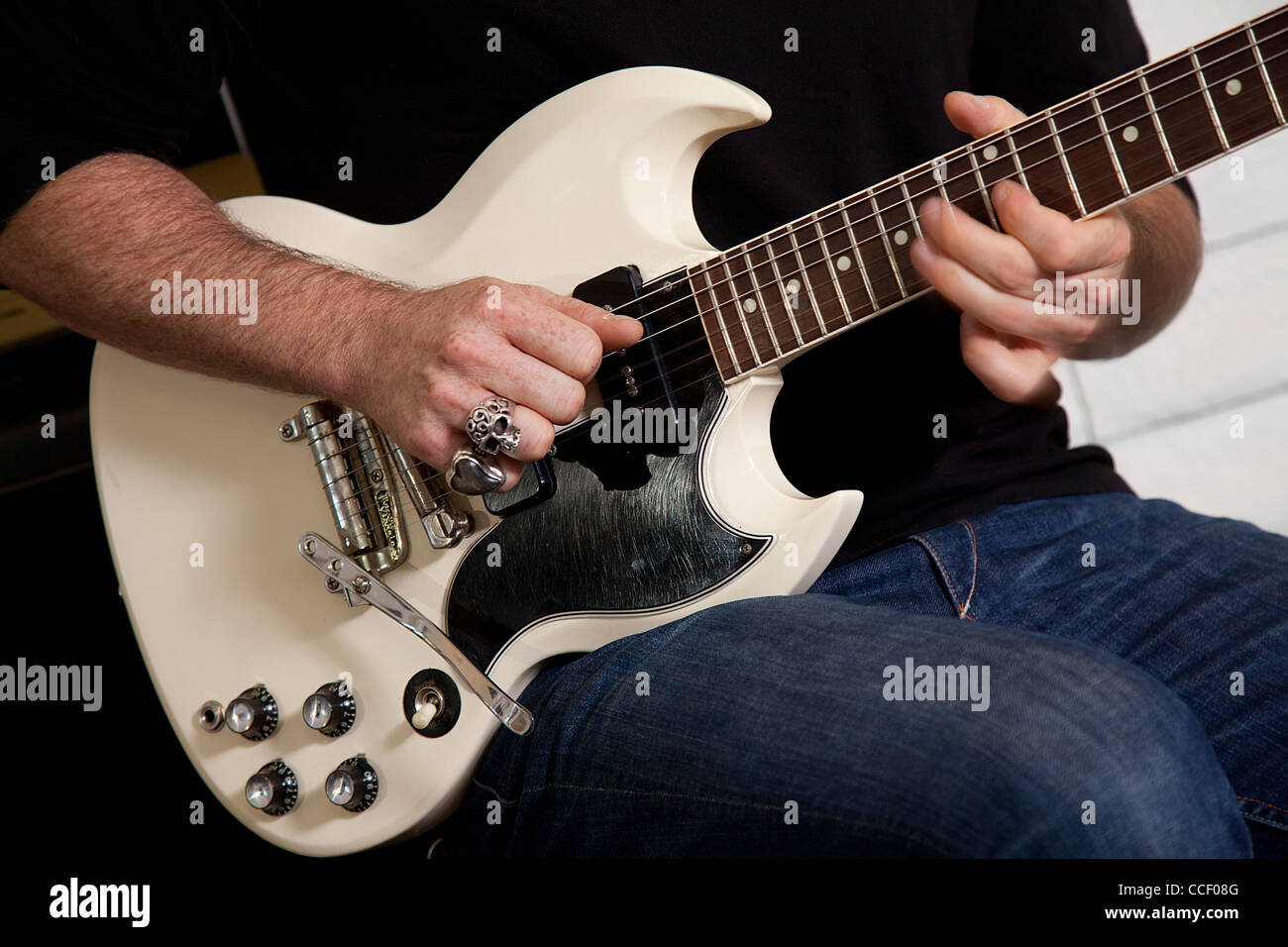 Close-up of mid adult man's torso playing guitar - Stock Image