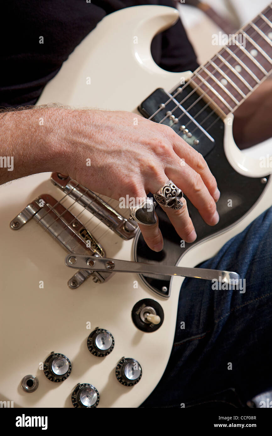 Close-up of man's hand playing electric guitar - Stock Image