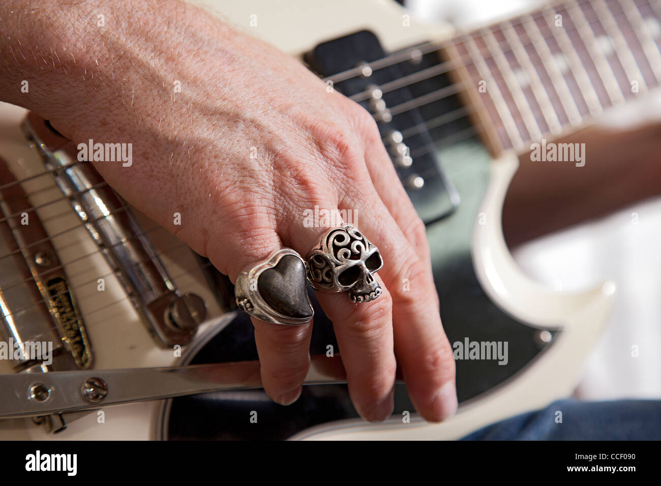 Close-up of mid adult man's fingers with rings playing guitar - Stock Image