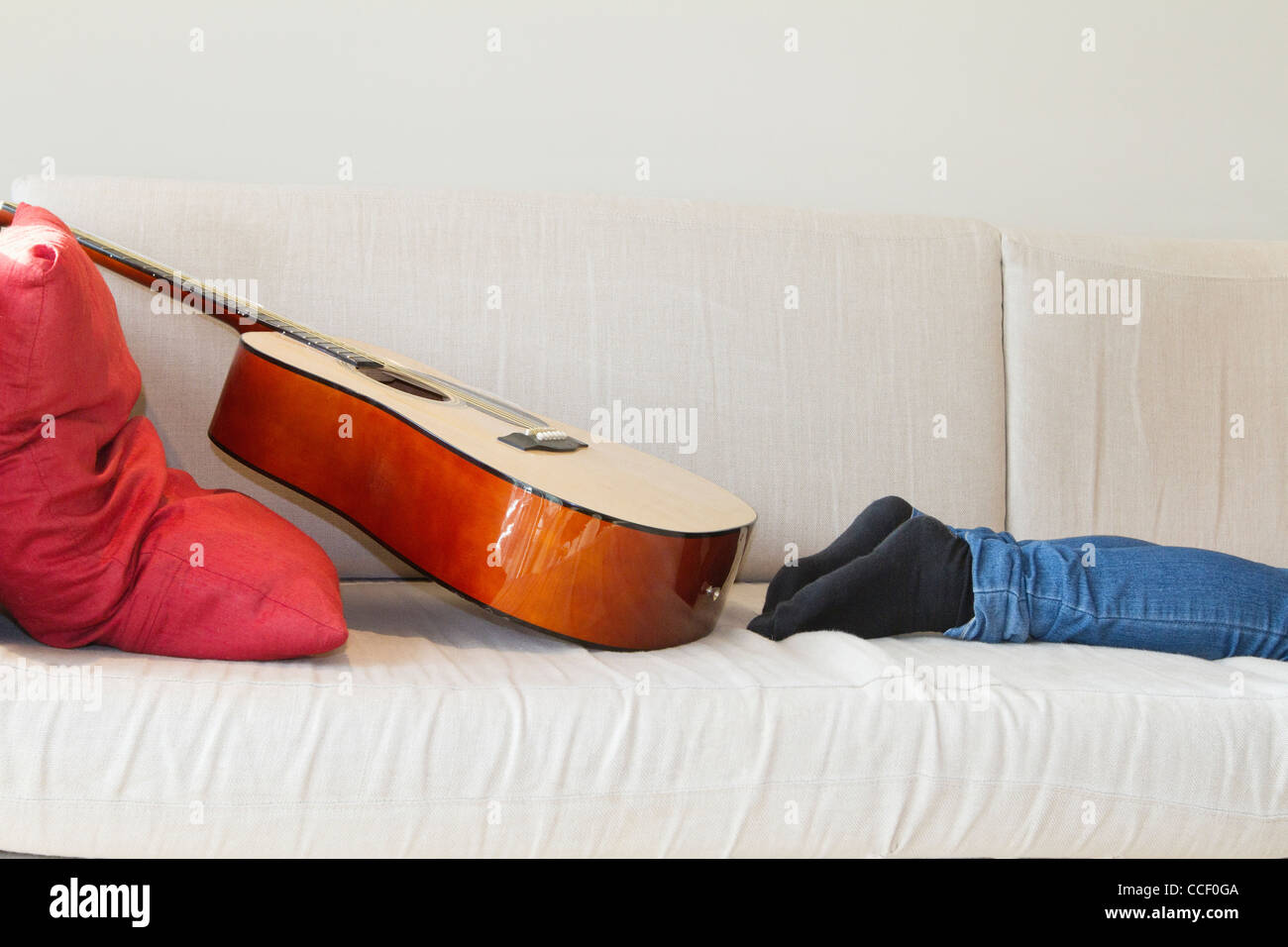 Low section of man's leg with guitar kept on sofa - Stock Image
