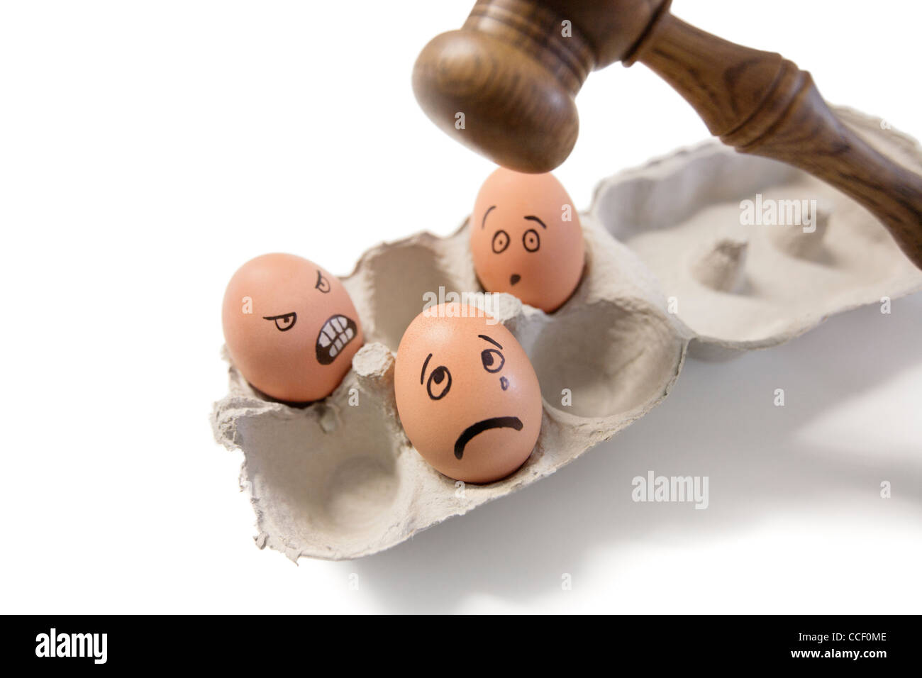 Funny faces on egg with gavel about to hit - Stock Image