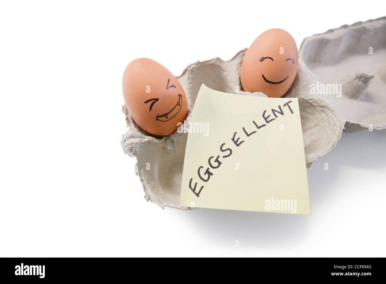 Smiley faces on eggs with 'eggsellent' written on notepaper - Stock Image