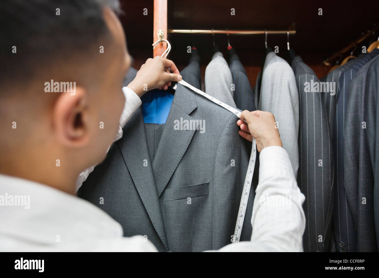 Tailor measuring shoulder of the suit - Stock Image