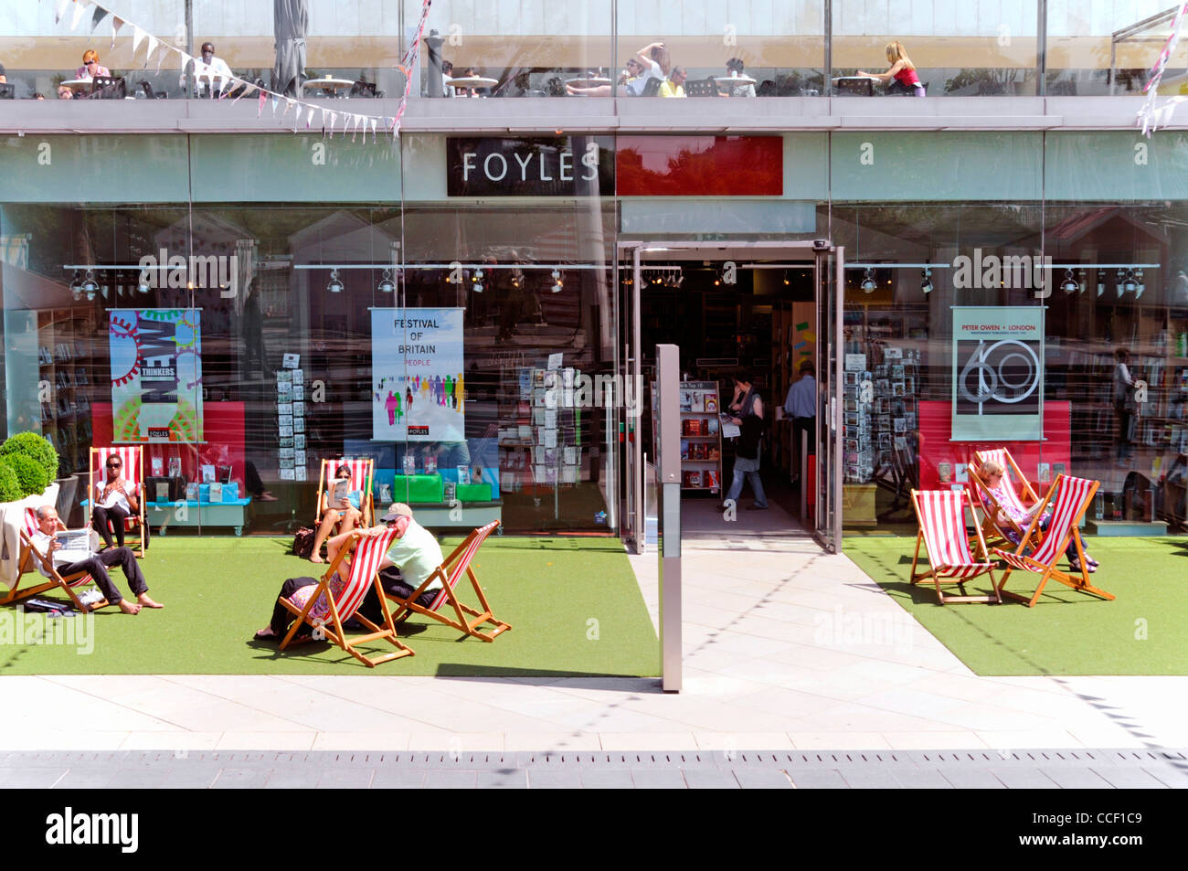 People enjoying summer sunshine sitting in deck chair outside the Foyles bookshop at Southbank Centre Lambeth London - Stock Image