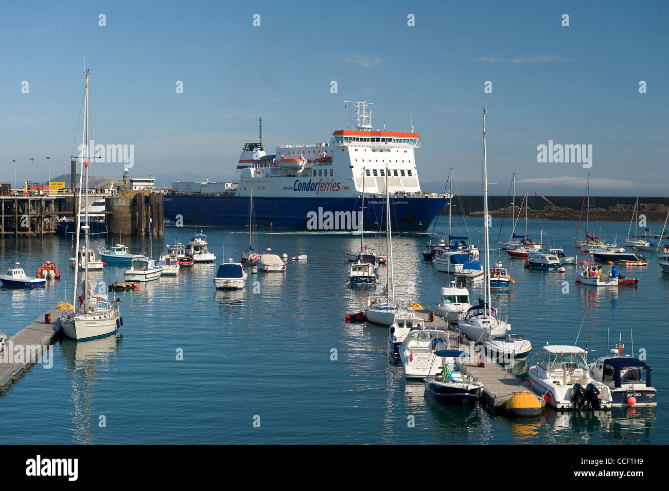 UK Channel Islands Guernsey Condor commercial shipping ferry entering St Peter Port harbour yachts in foreground Stock Photo