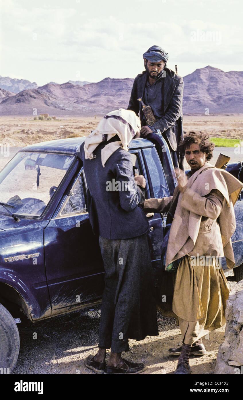 Three Yemini men standing by a pickup truck in Marib Governorate, Yemen - Stock Image