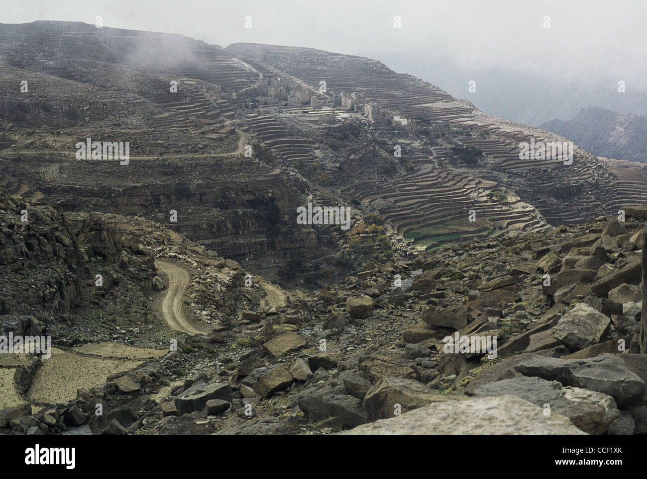 Terraced farmland and a distant view of a village in the mountains of Hajjah Governorate, Yemen - Stock Image