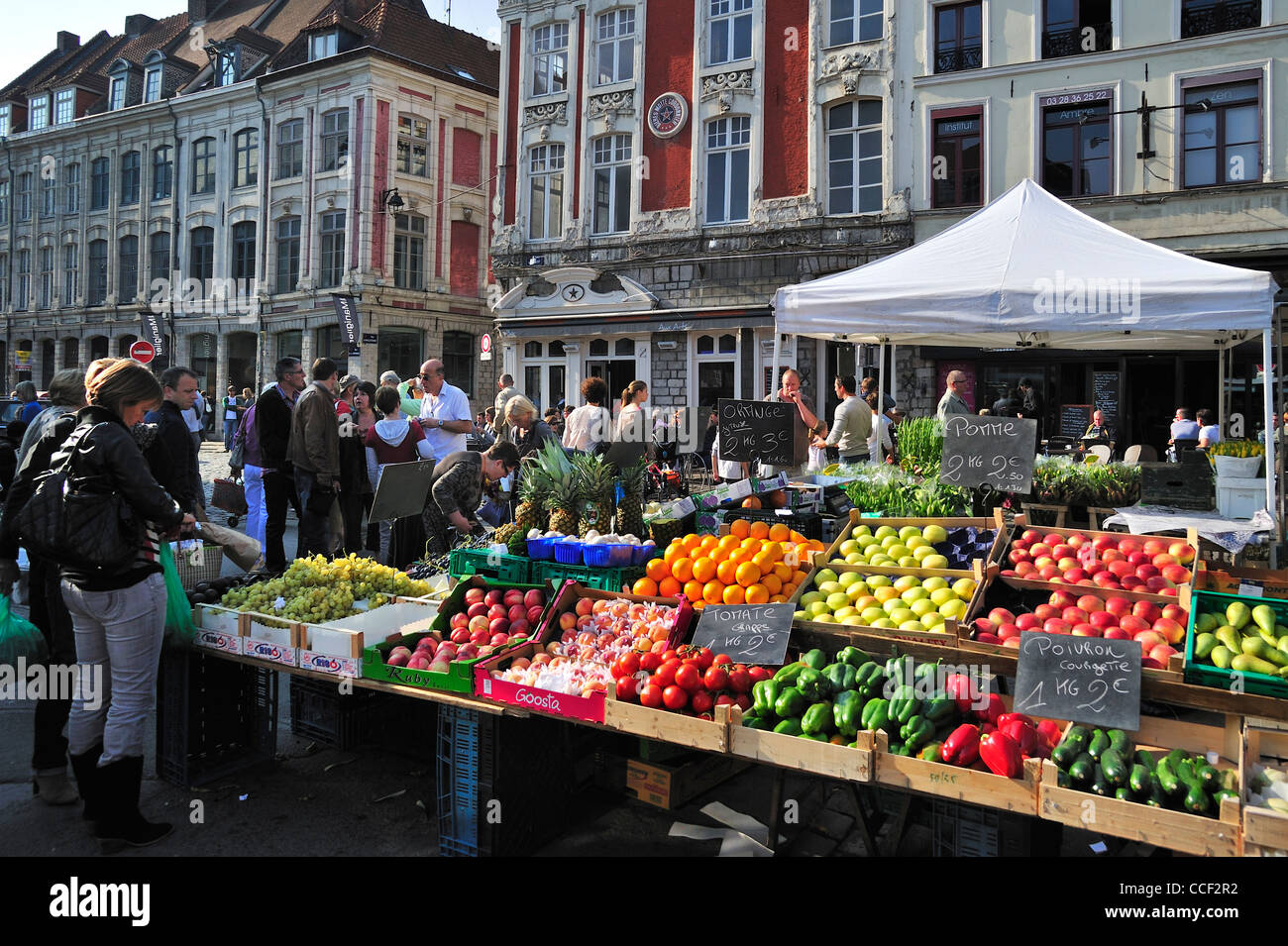 Customers buying fruit and vegetables at market stall, Lille, France - Stock Image