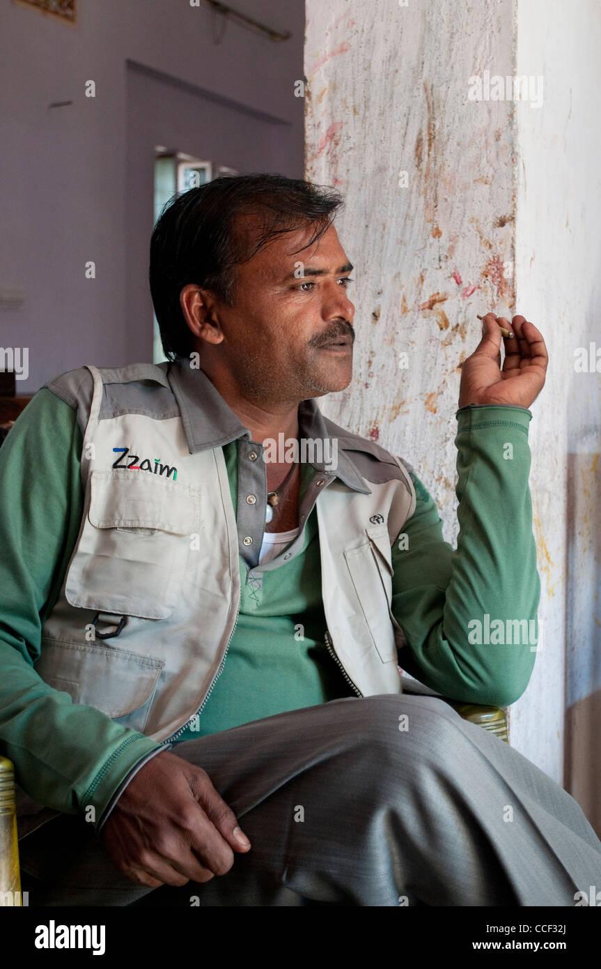 Middle-aged Rajasthani man in pensive mood smoking, Fabric block printing workshop, Bagru village, Jaipur, Rajasthan, Stock Photo