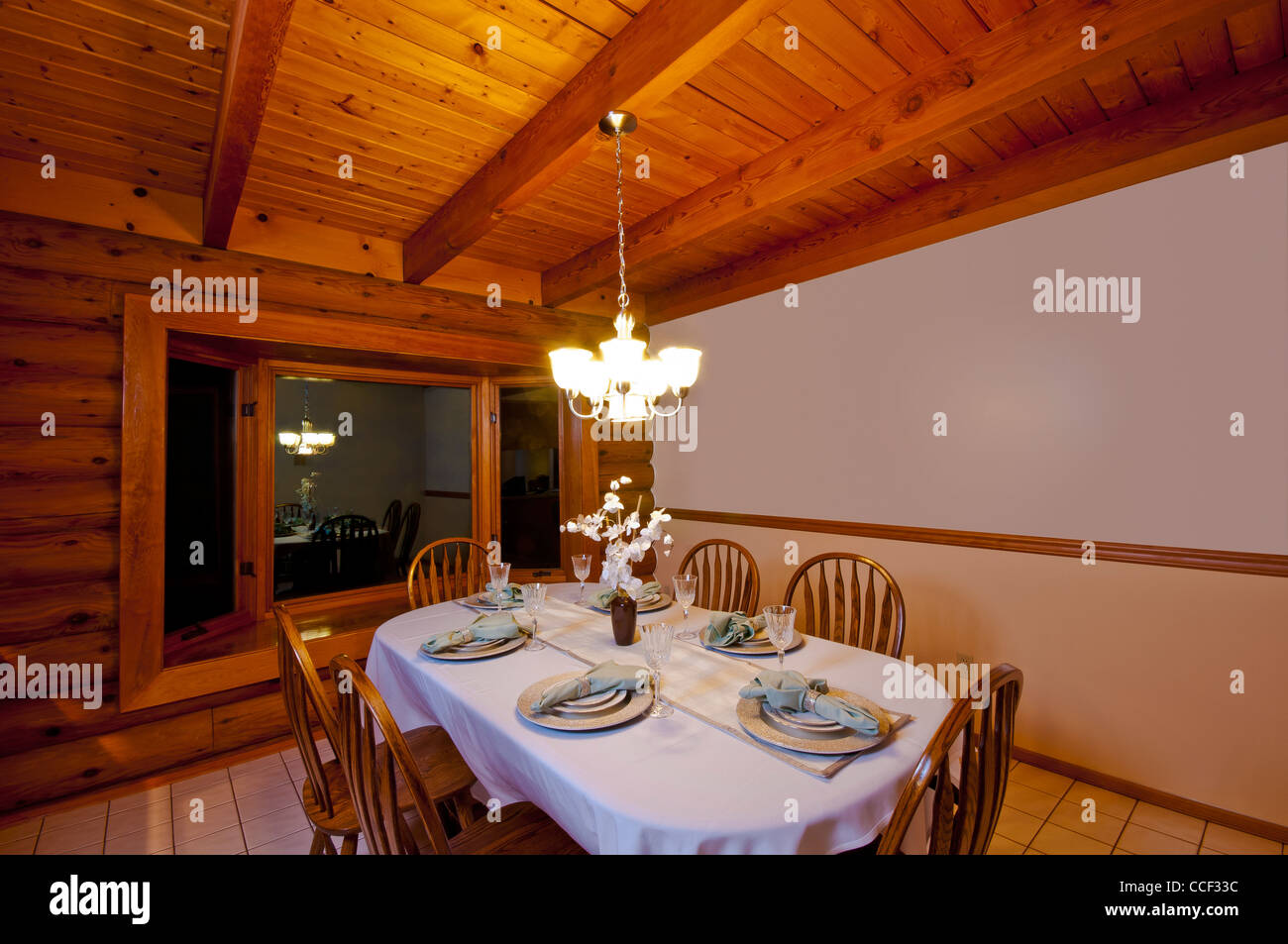 Dining room in rustic luxury log cabin showing table, chairs Stock ...