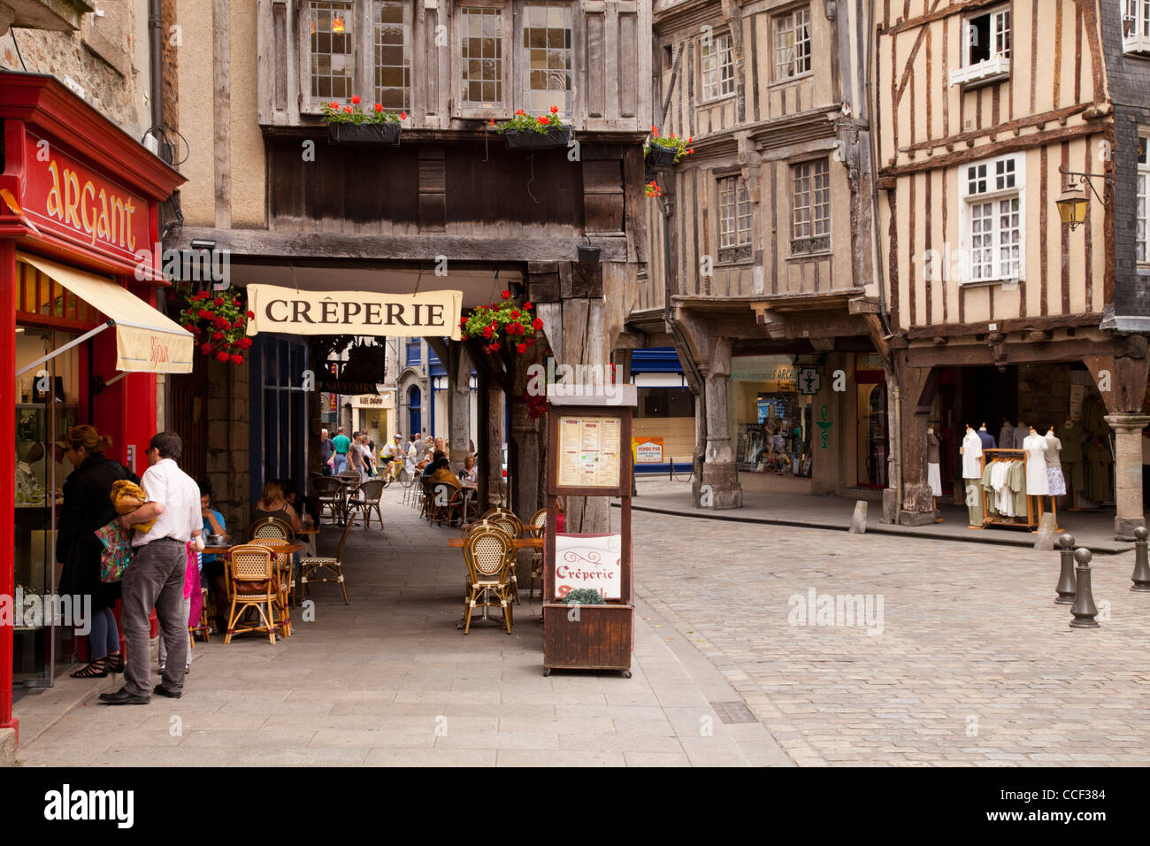 Shops, restaurants and ancient half timbered buildings in the medieval centre of Dinan, Brittany, France. - Stock Image
