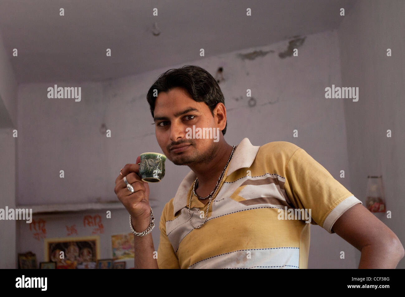 Young Rajasthani man drinking tea, Fabric block printing workshop, Bagru village, Jaipur, Rajasthan, India Stock Photo