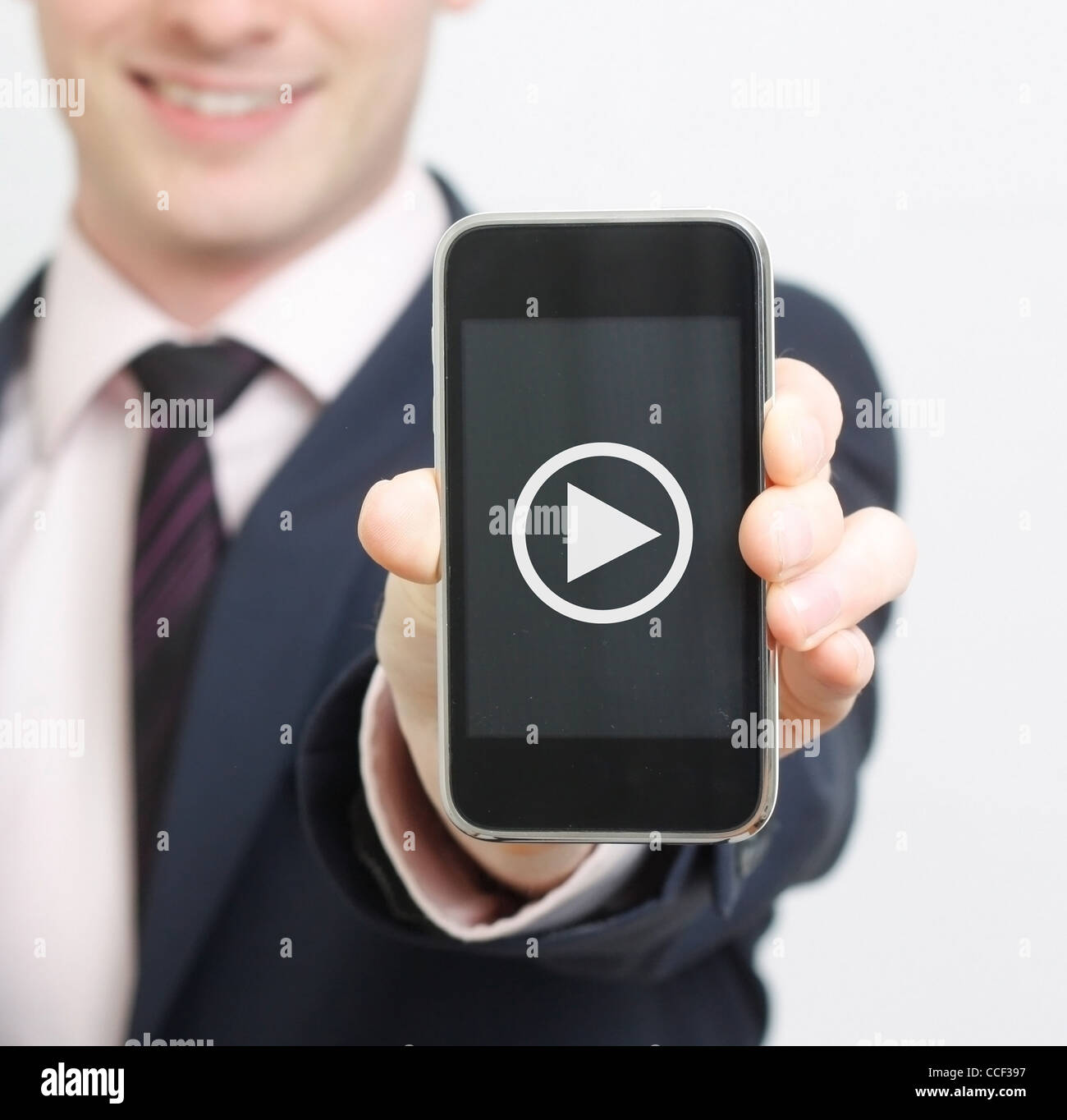 A business man showing his phone with video button - Stock Image