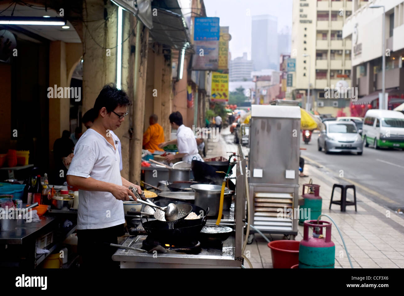 Local man cooking fast food on the street in Kuala Lumpur's Chinatown. KL Chinatown is a popular tourist attraction - Stock Image