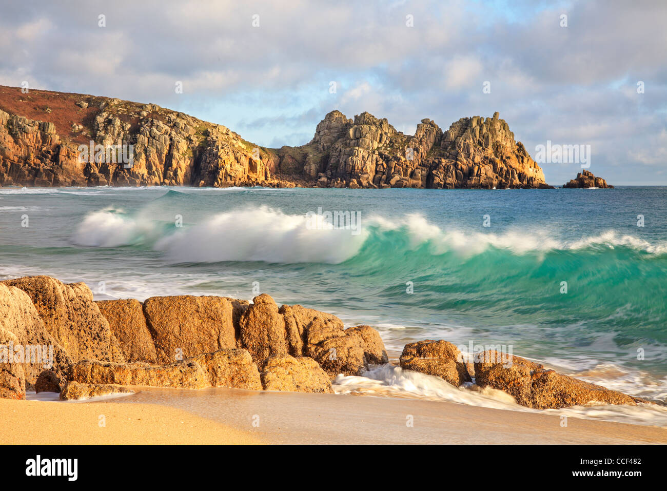 A breaking wave captured from Porthcurno Beach in Cornwall with Logan Rock in the distance - Stock Image