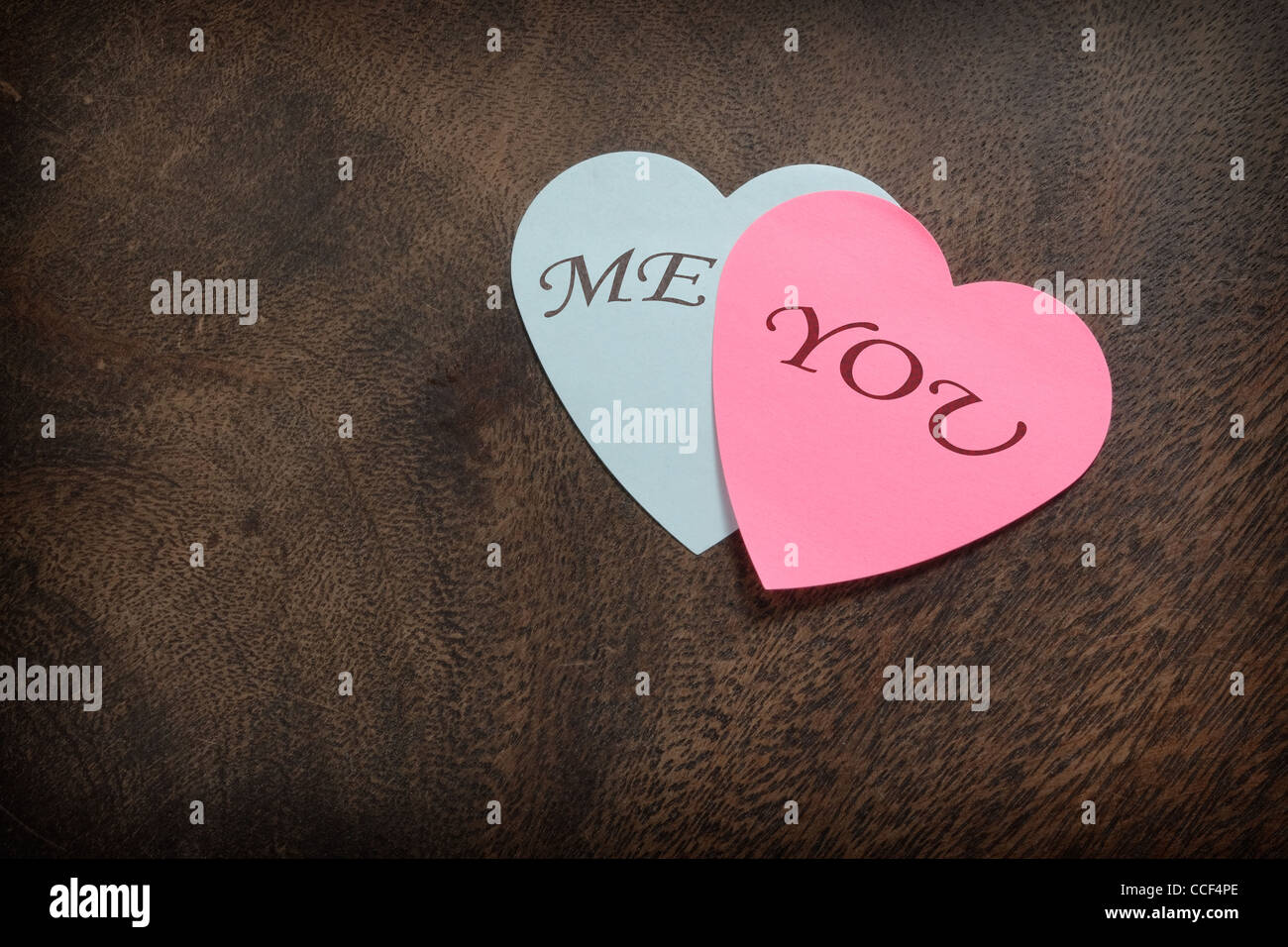 Heart shaped sticky notes on wooden background - Stock Image