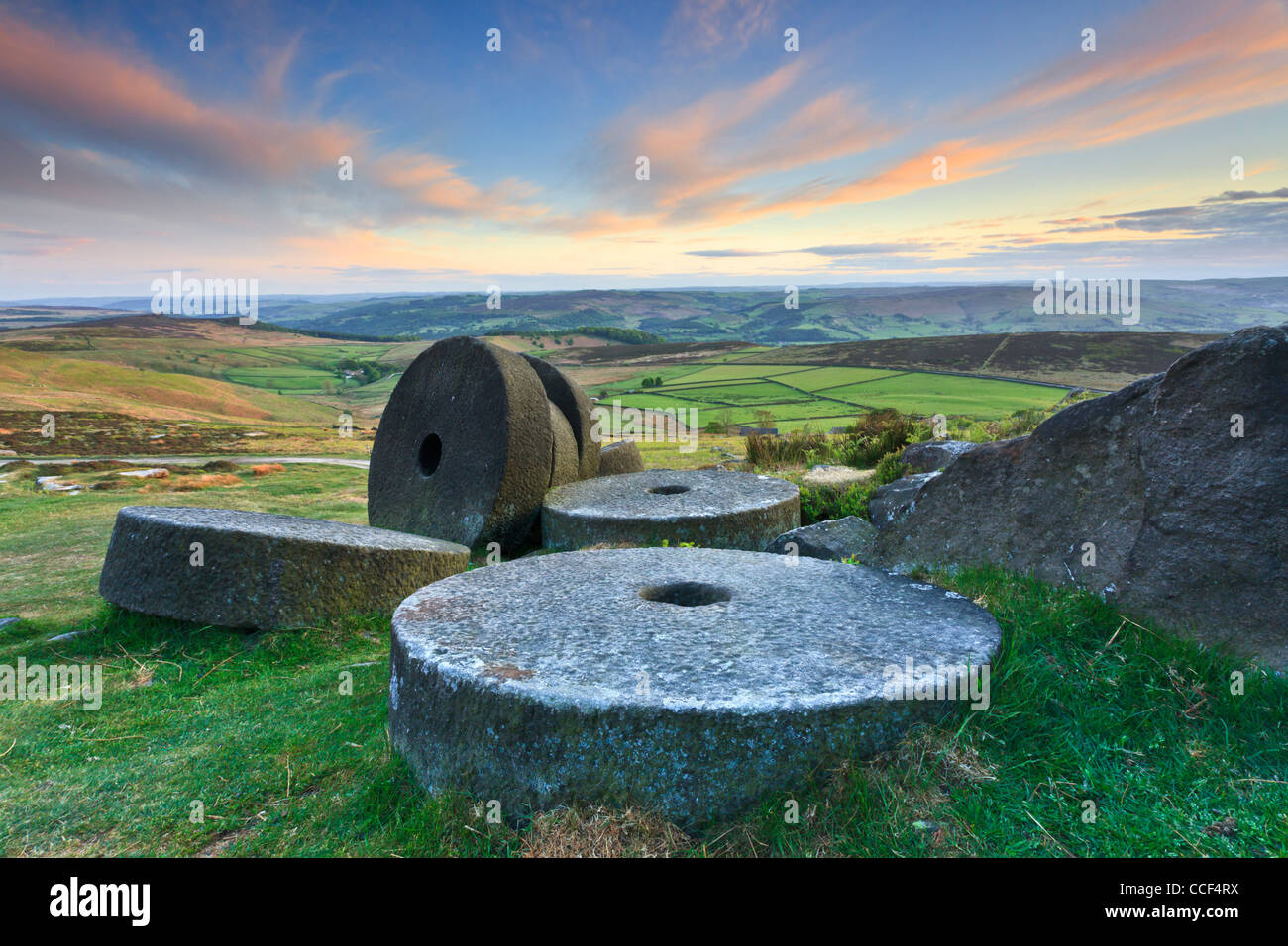 Millstones on Stanage Edge in the Peak District National Park.  Captured at sunset with the Hope Valley in the distance - Stock Image