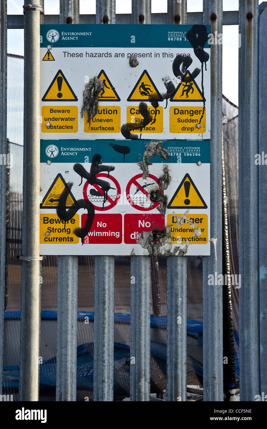 A defaced sign on a metal fence - Stock Image
