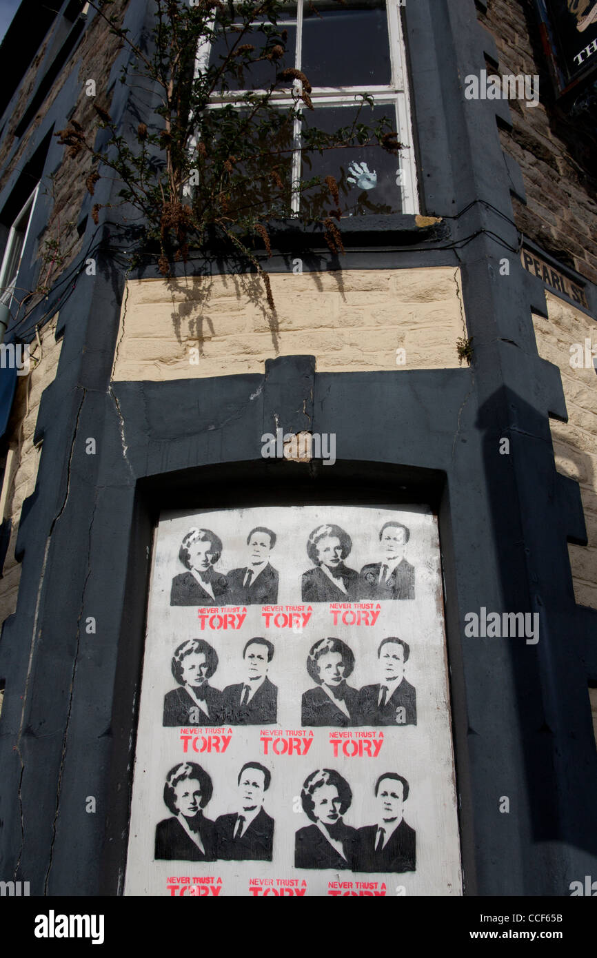 'Never Trust a Tory' stencil poster art with Prime Ministers Thatcher and Cameron on boarded-up derelict - Stock Image