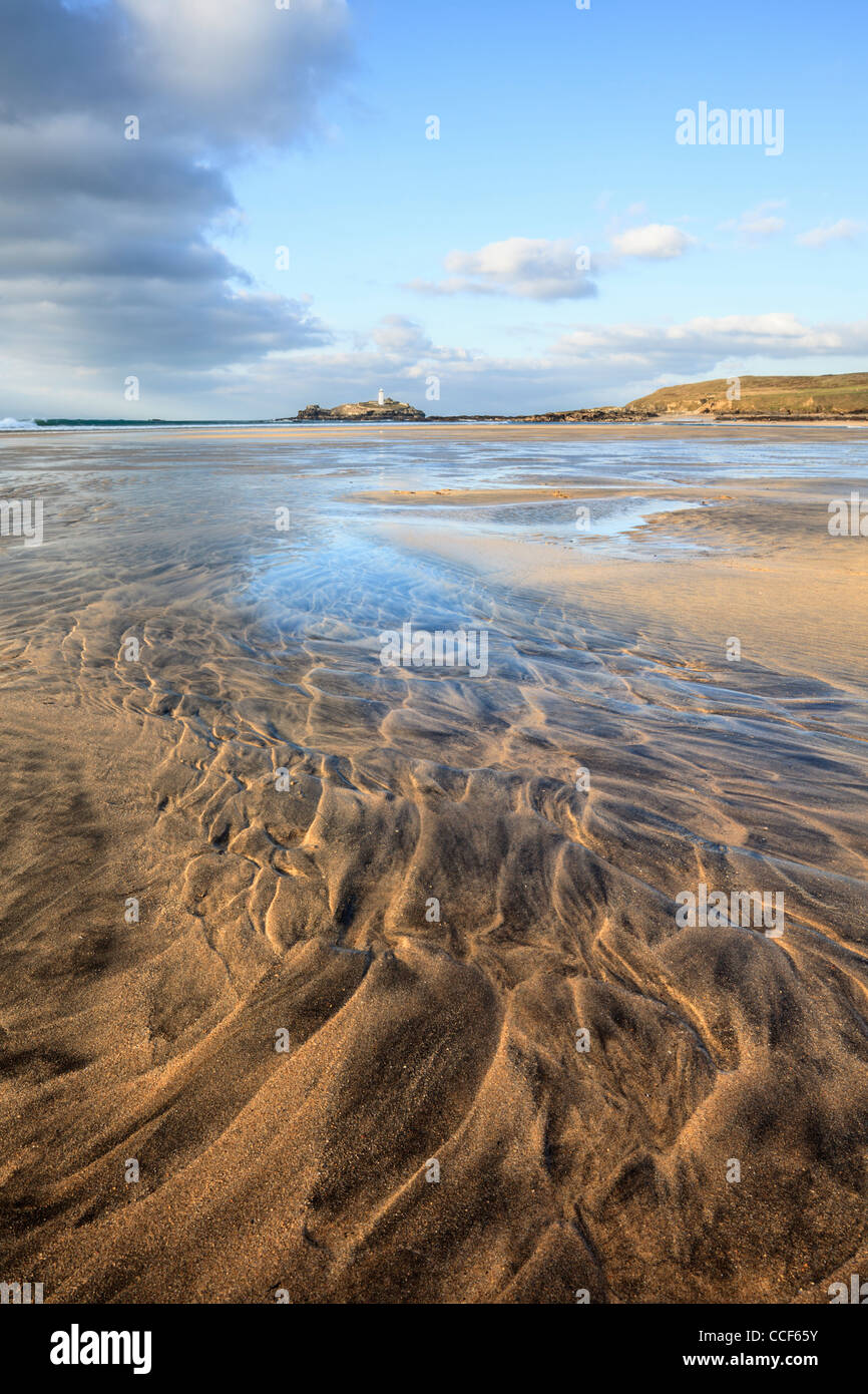 Sand Patterns on Godrevy Beach in Cornwall lead the eye towards the lighthouse and island - Stock Image