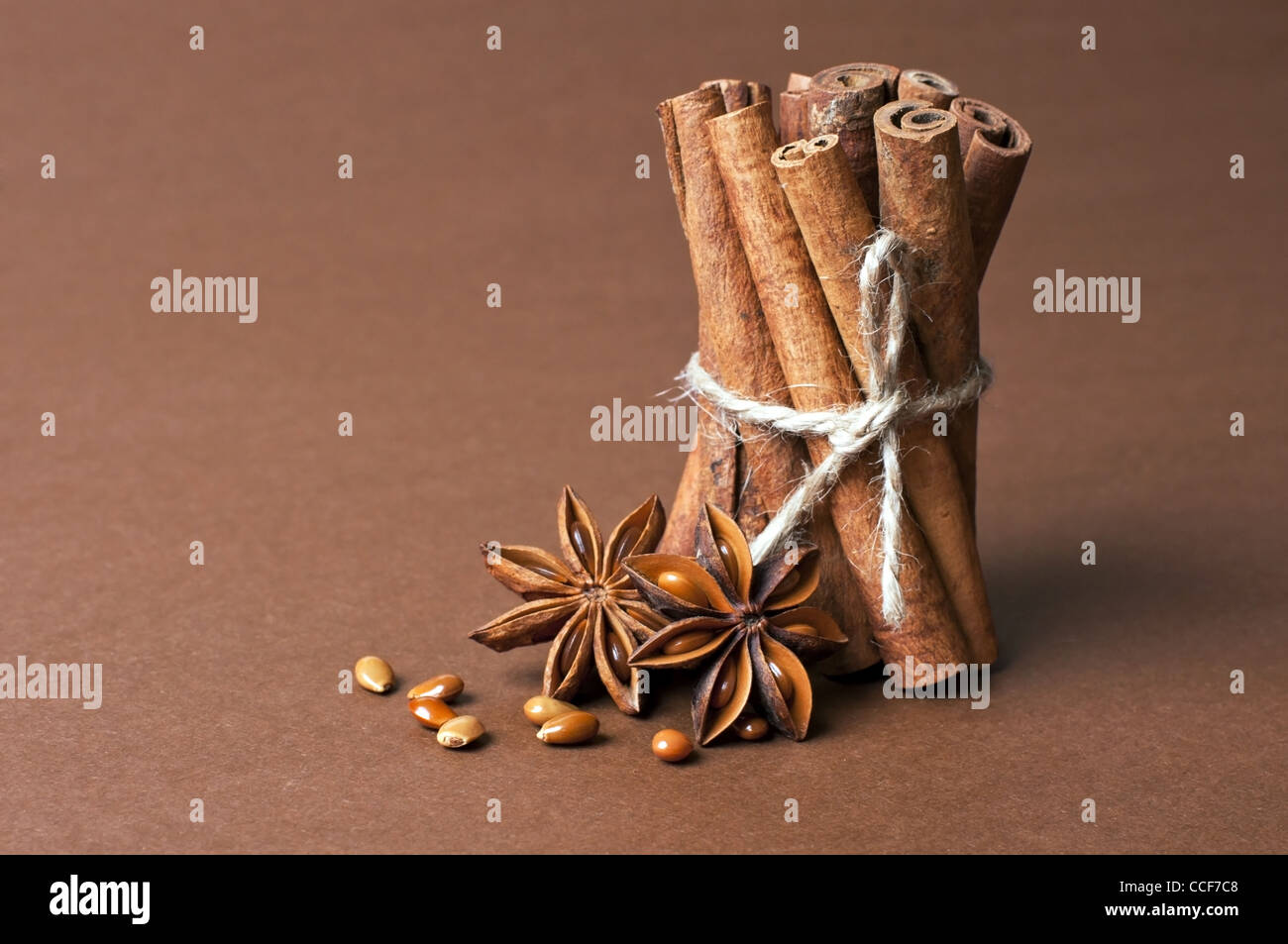 Cinnamon stick and anise stars on brown background - Stock Image
