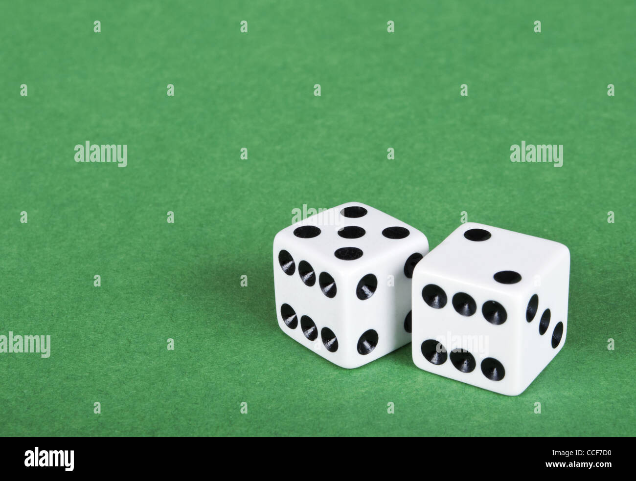 Two white dices on green background - Stock Image