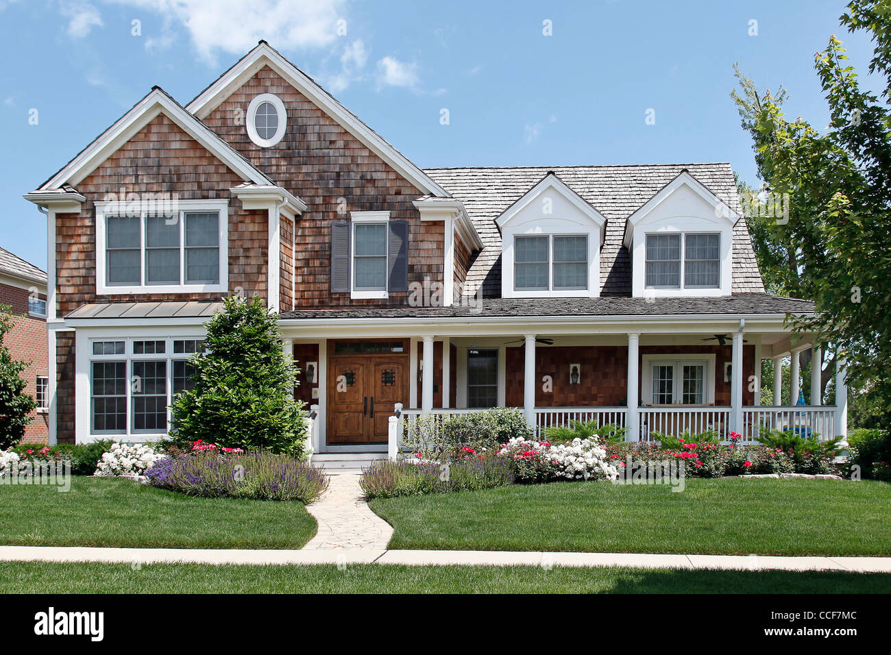 Suburban Home With Flowered Landscaping And Front Porch Stock
