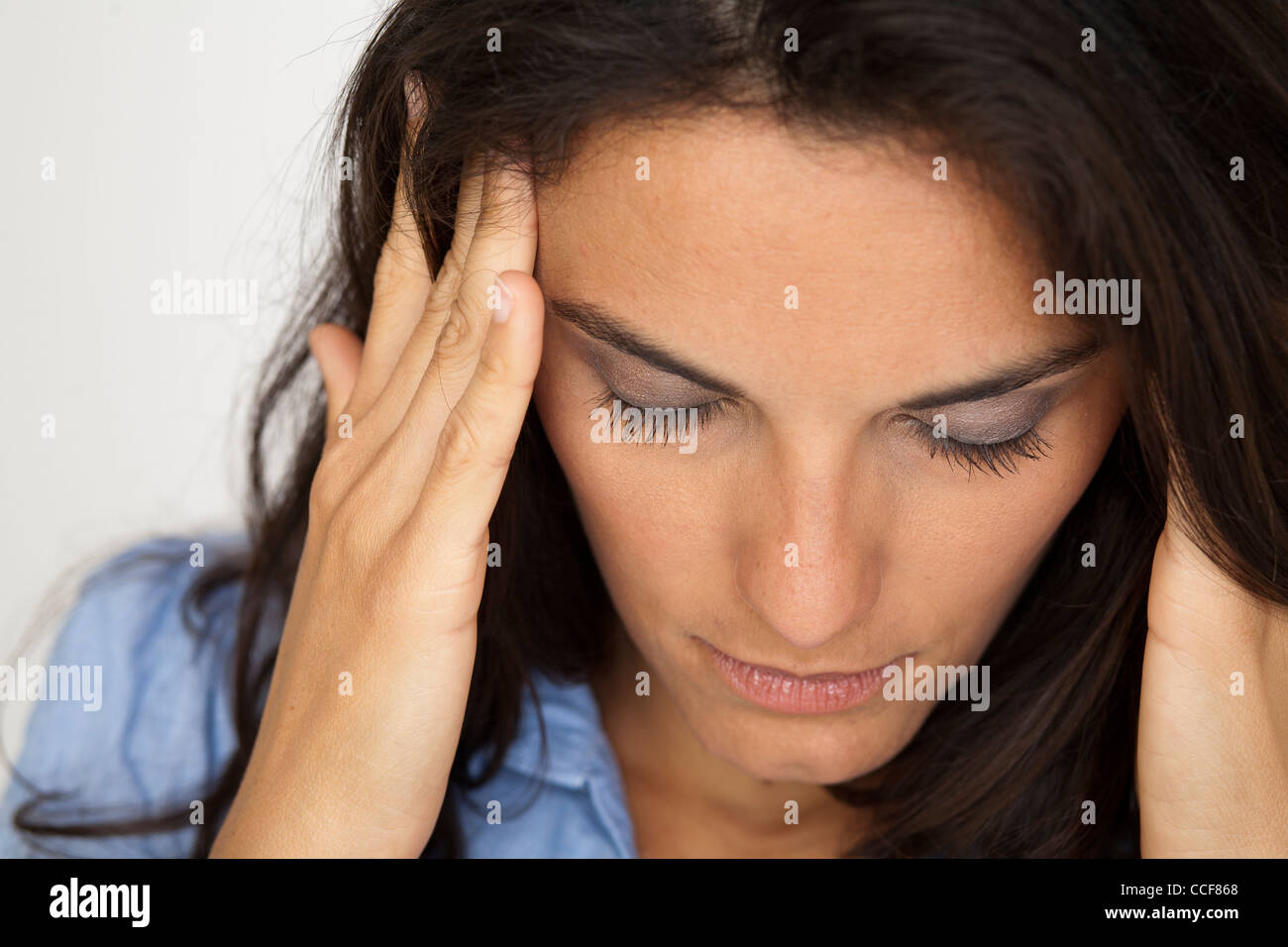 Latin woman suffering from headache Stock Photo