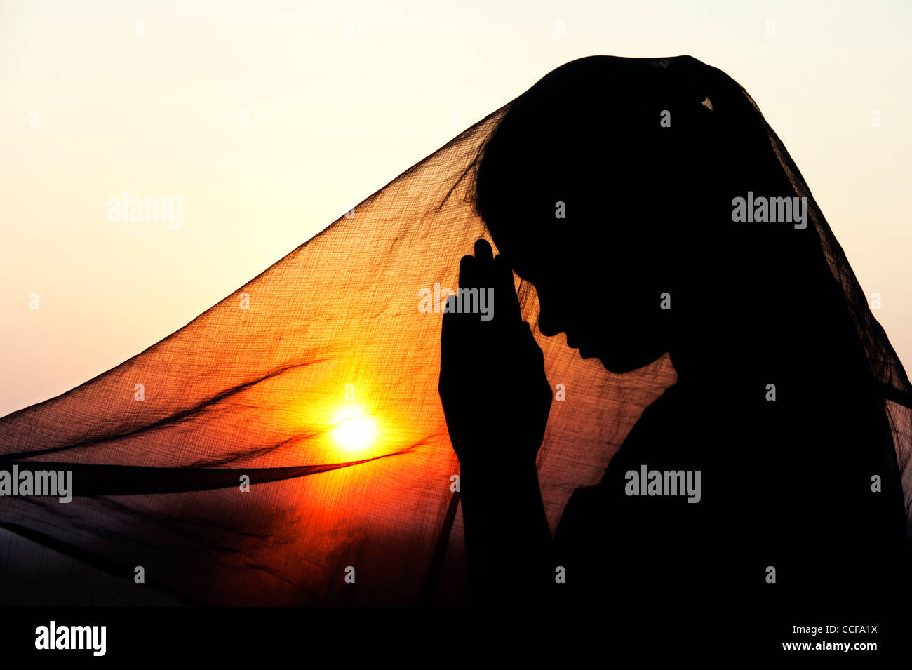 Indian teenage girl praying at sunset covered by a veil. Silhouette. India - Stock Image