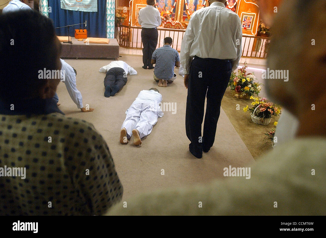 Male devotees at the Swaminarayan Hindu Temple in North San Antonio prostrate in front of the idol after the prayer - Stock Image