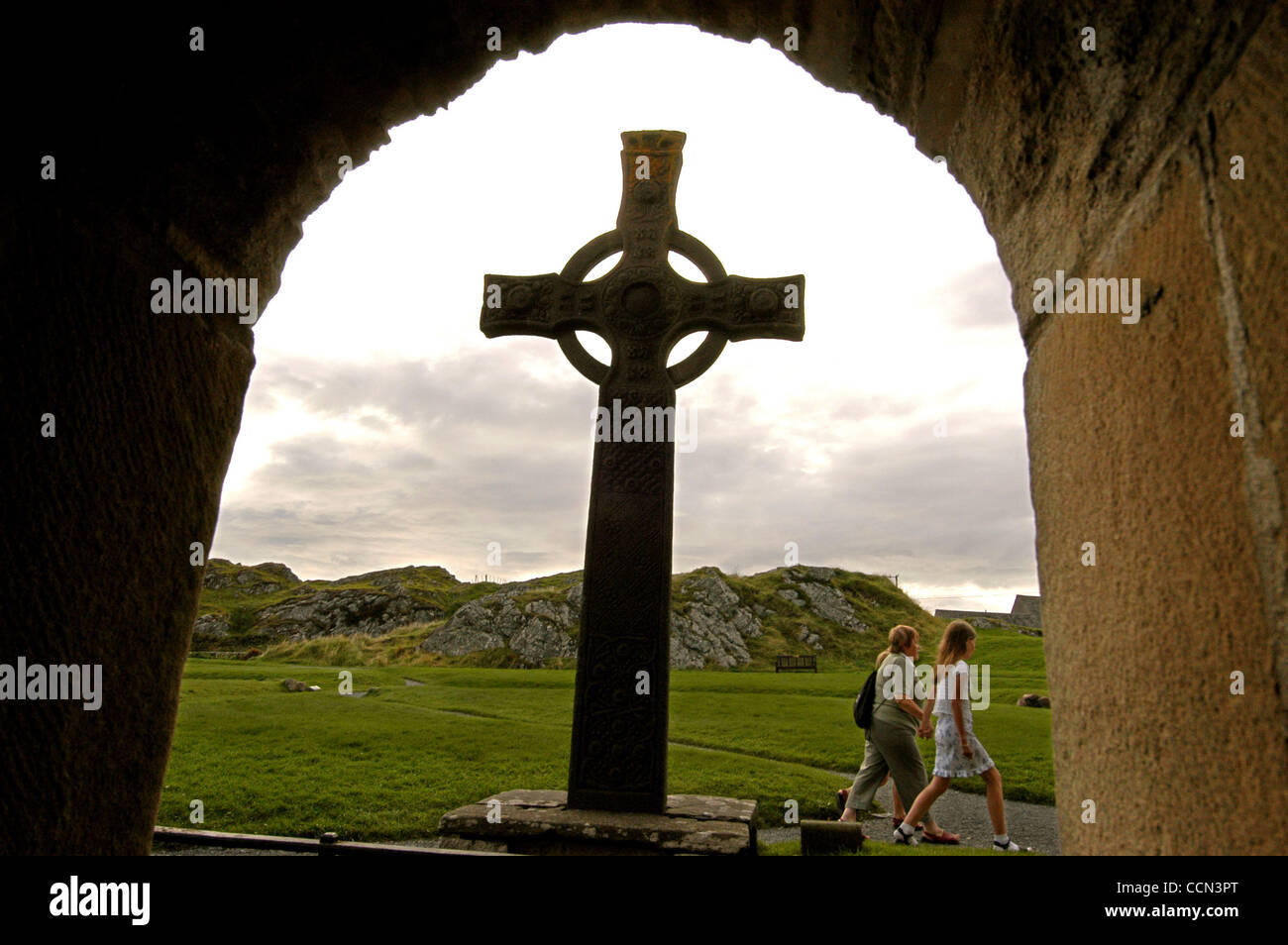 mother and daughters walk to evening prayer services at Abbey on the tiny isle of Iona, where Christiany was first - Stock Image