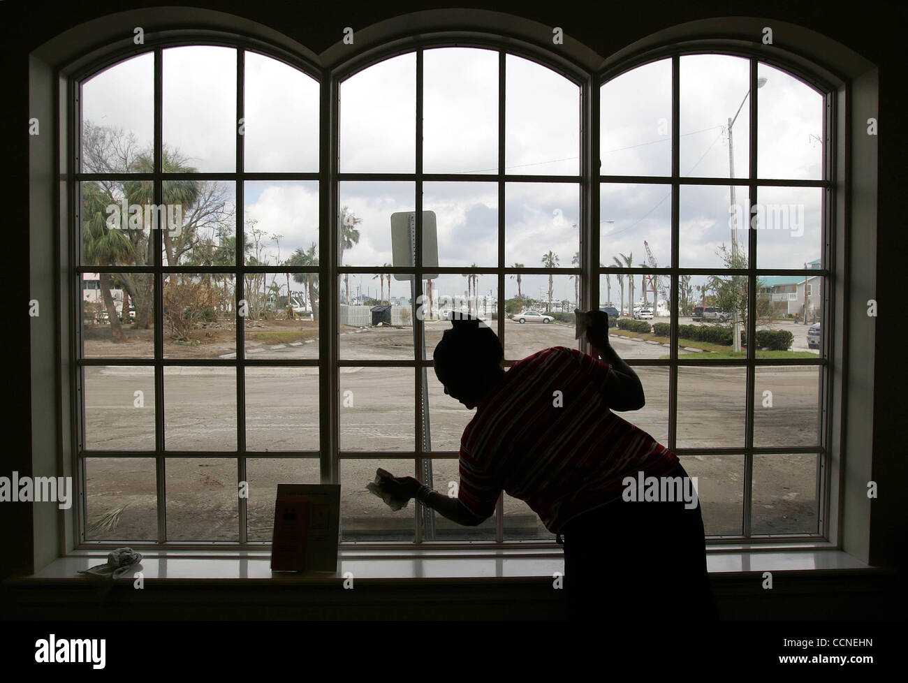 092904 - PT. ST. LUCIE, FL -interlibrary loan service employee Mary Jane Neal, cleans windows from hurricane Jeanne - Stock Image