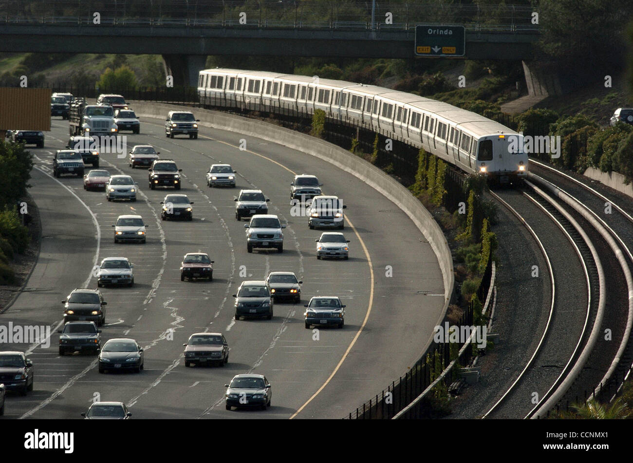 An eastbound BART train races afternoon traffic on Highway 24 through Orinda Tuesday. Voters face a number of transportation - Stock Image