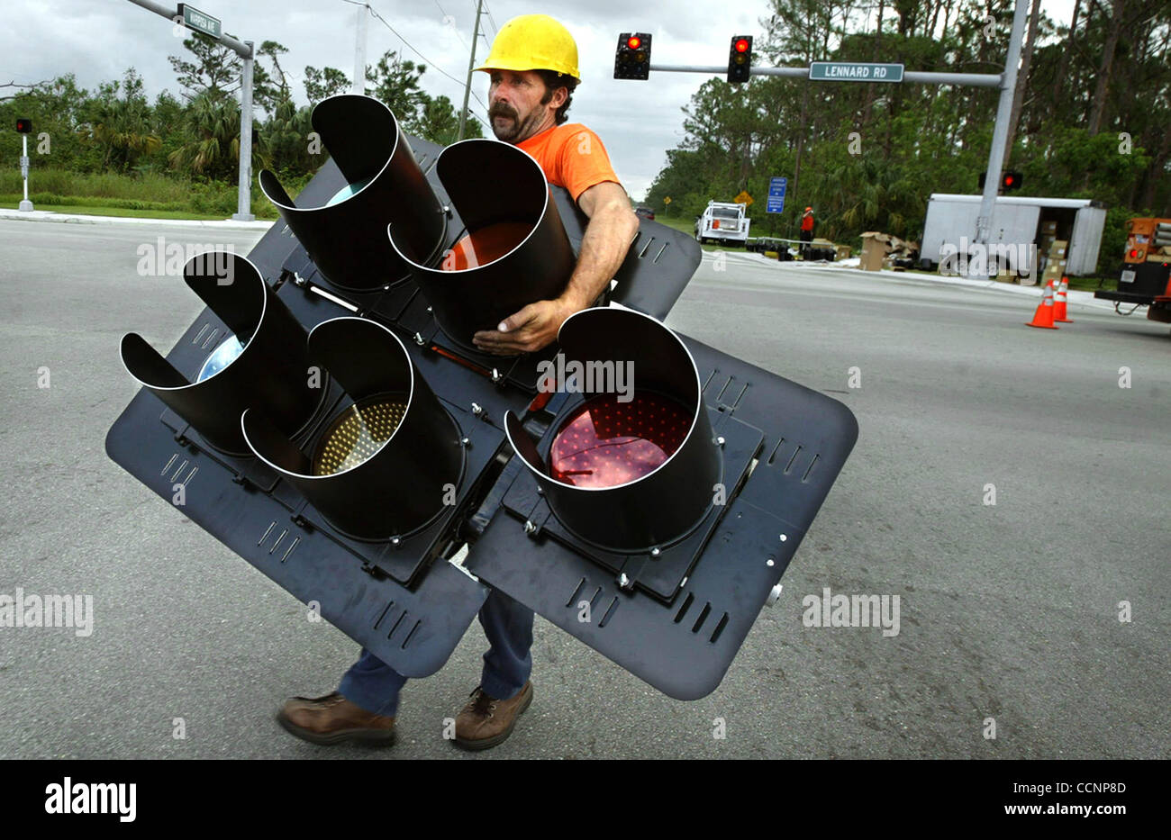 111704 TC MET Port St. Lucie...American Lighting & Signalization employee David Guy (cq) lugs a five-section - Stock Image