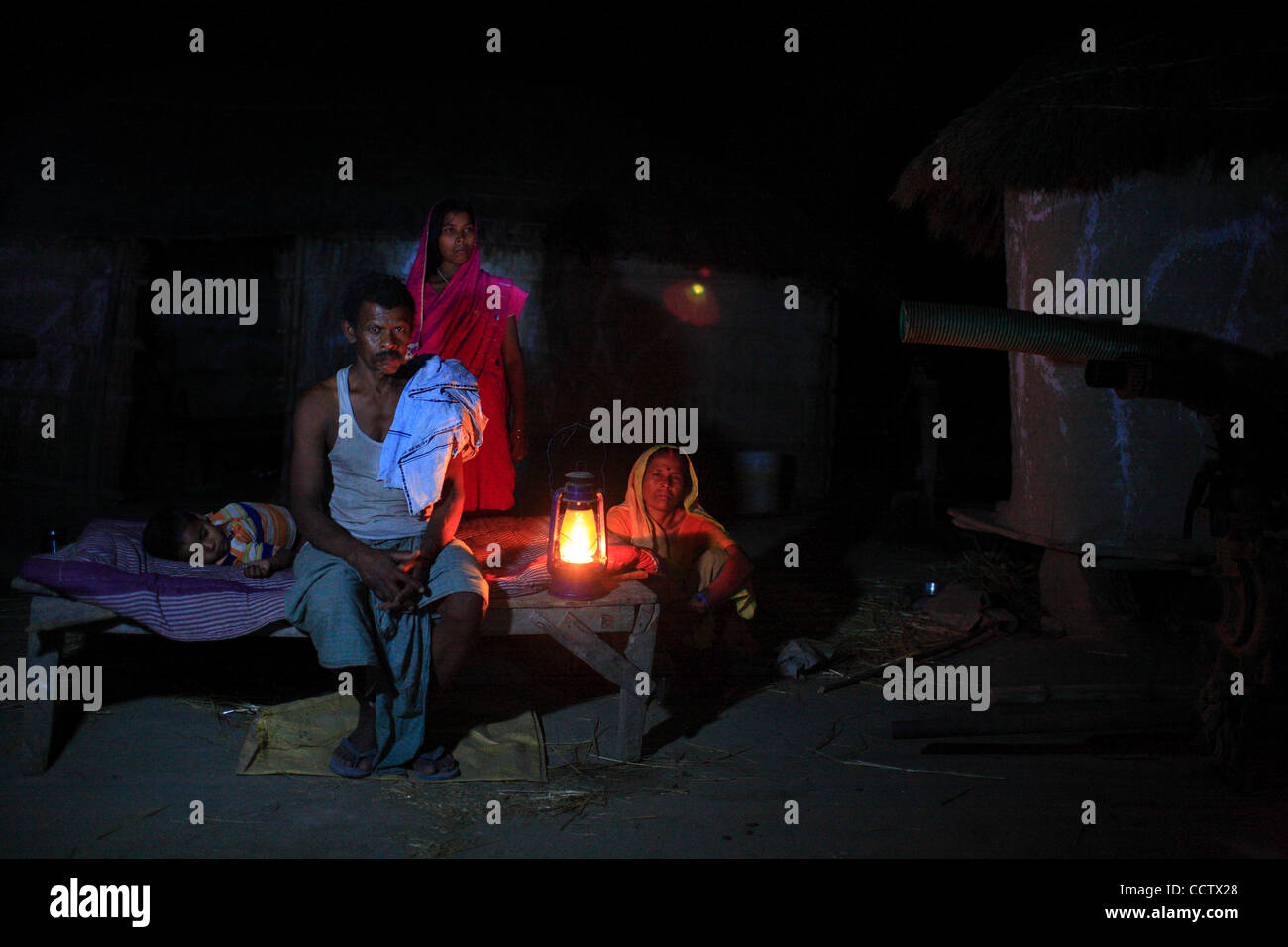 Ramprit Mahato at his home in  village Tamkuha with his family sits in the darkness in the dim light of a kerosene - Stock Image