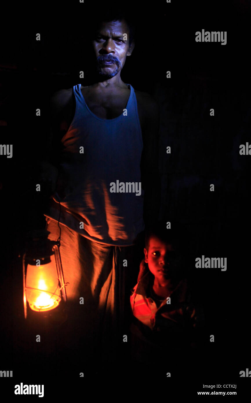 Ramprit Mahato at his home in  village Tamkuha with his son  in the dim light of a kerosene lamp. He cannot afford - Stock Image