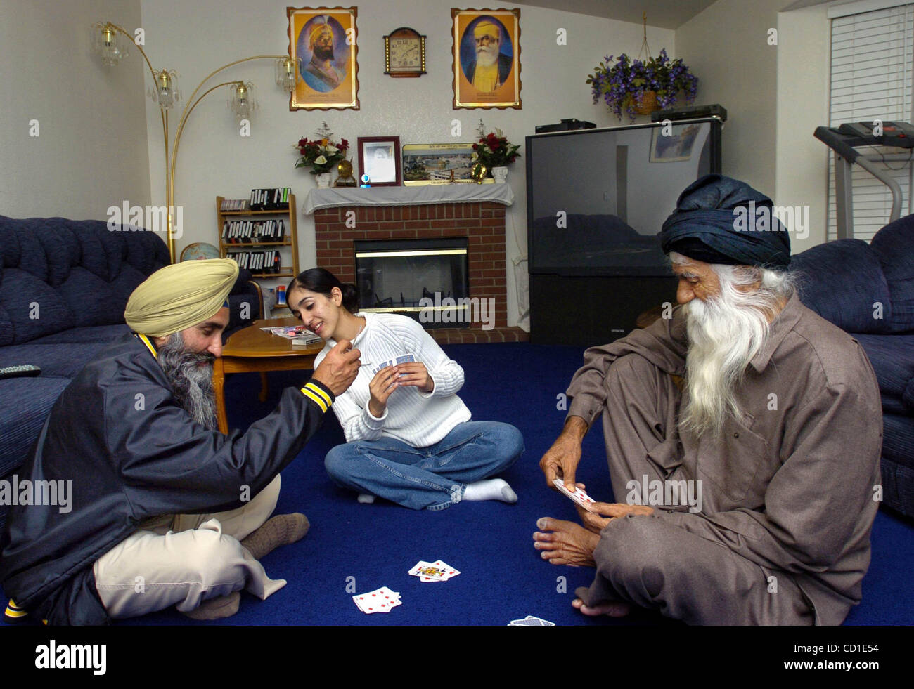 VET PROJECT:  Ranbir Kaur, cq, 19, center, checks out the cards of her 45-year-old dad Mahan Nijjar, cq, 45, left, - Stock Image