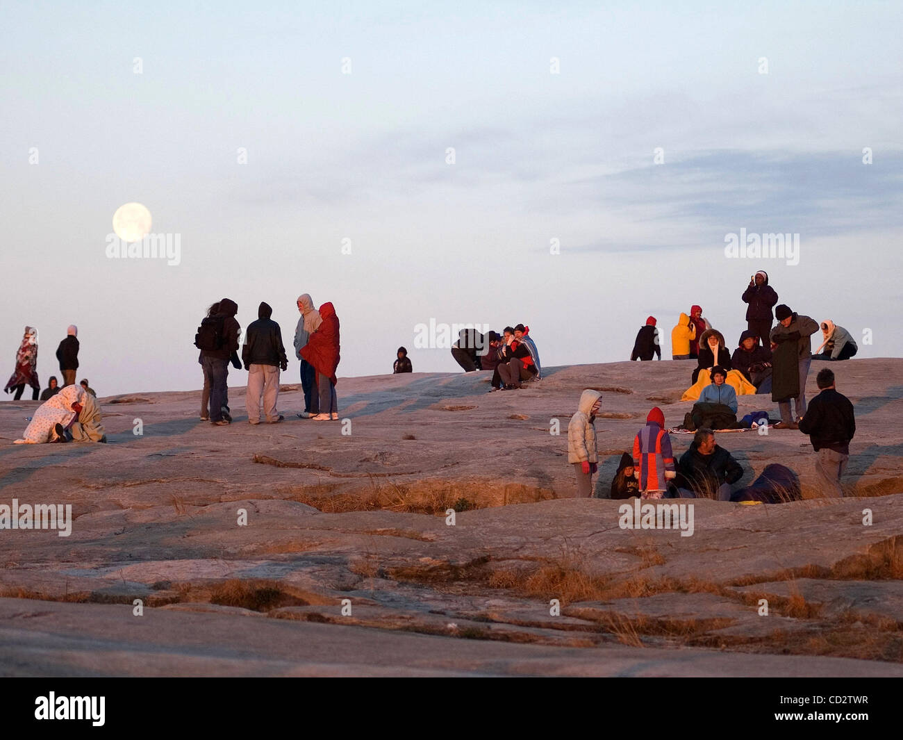 Worshipers watch as the sun rises during the Easter Sunrise Service on the top of Stone Mountain, Ga. as the moon Stock Photo