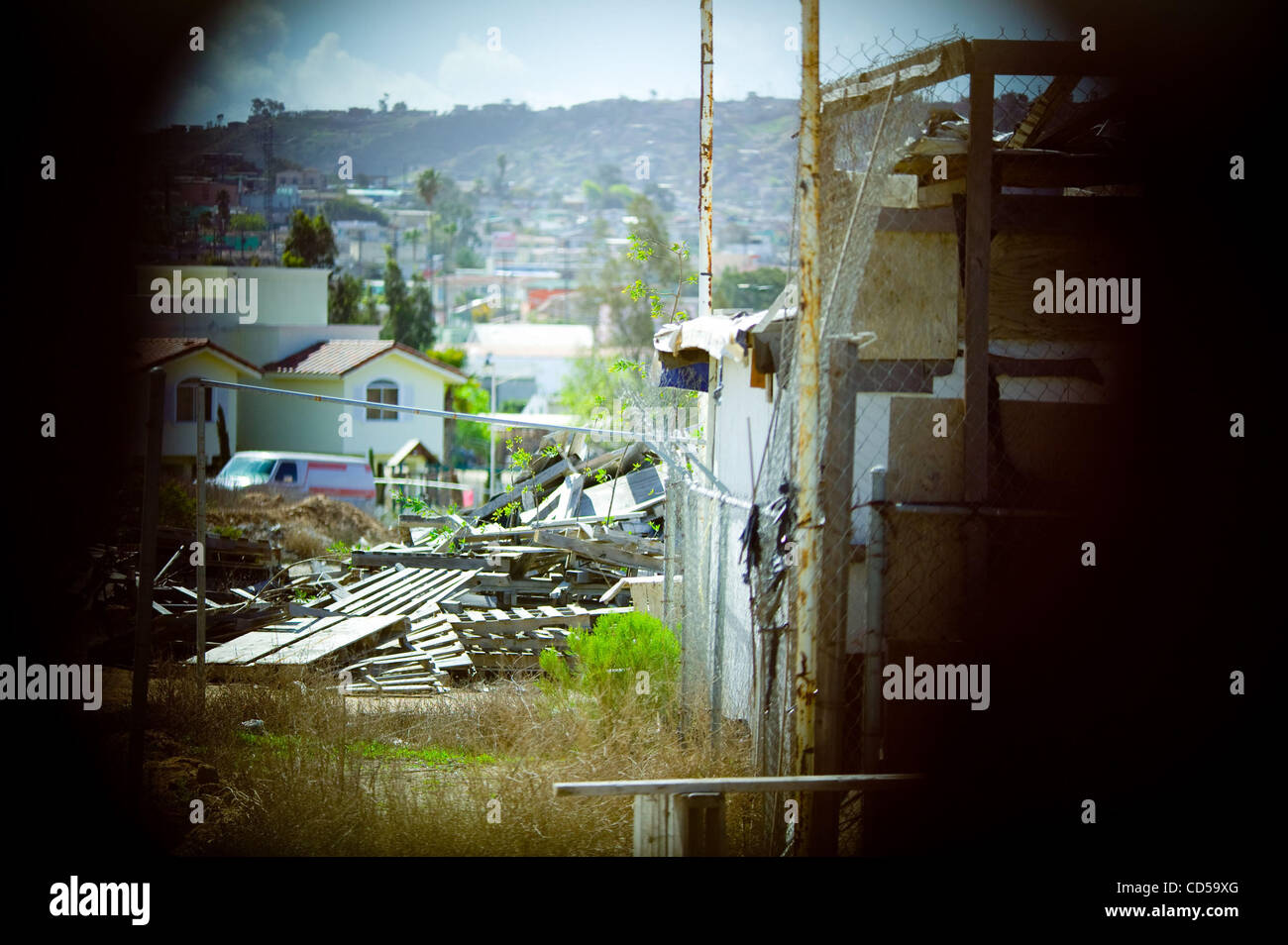 Tijuana viewed from the American side through a hole in the border wall Stock Photo