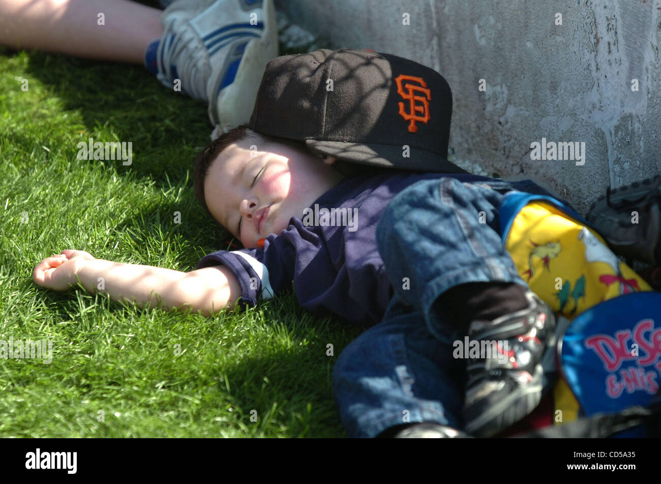 San Francisco Giants fan Rohan Rustvold of Albuquerque, New Mexico snoozes as his team loses badly to the Oakland - Stock Image