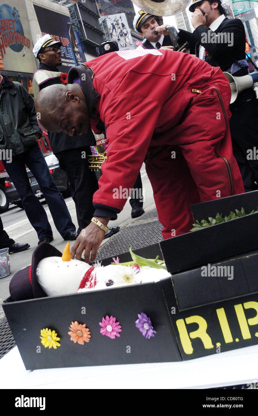 Times Square Alliance employee Lenny Gideon drops a tulip into the mock coffin. Times Square mourns the death of - Stock Image