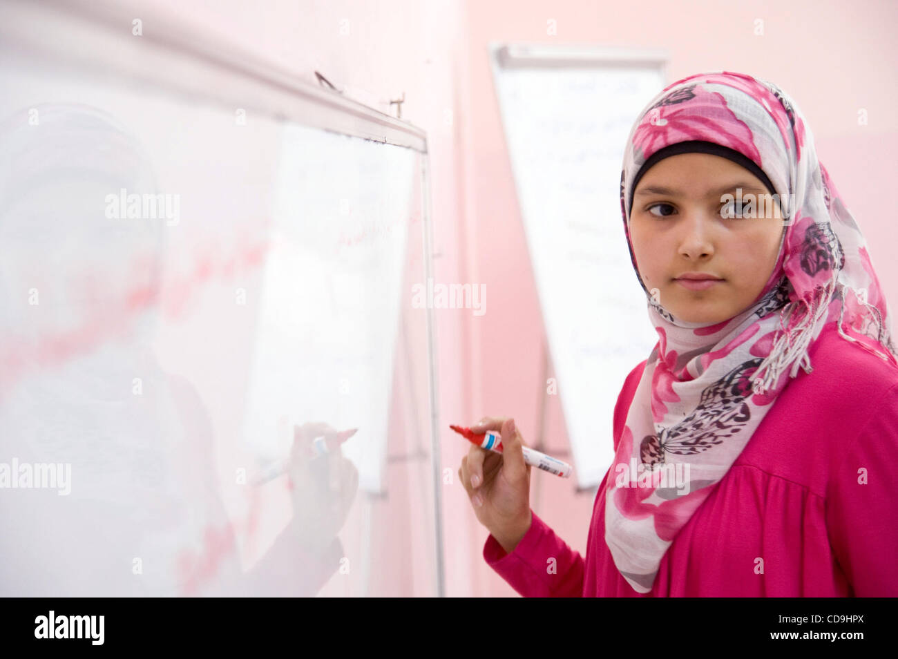 July 12, 2010 - Amman, Jordan - July 12, 2010, Amman, Jordan - A girl completes a lesson on the white board during - Stock Image