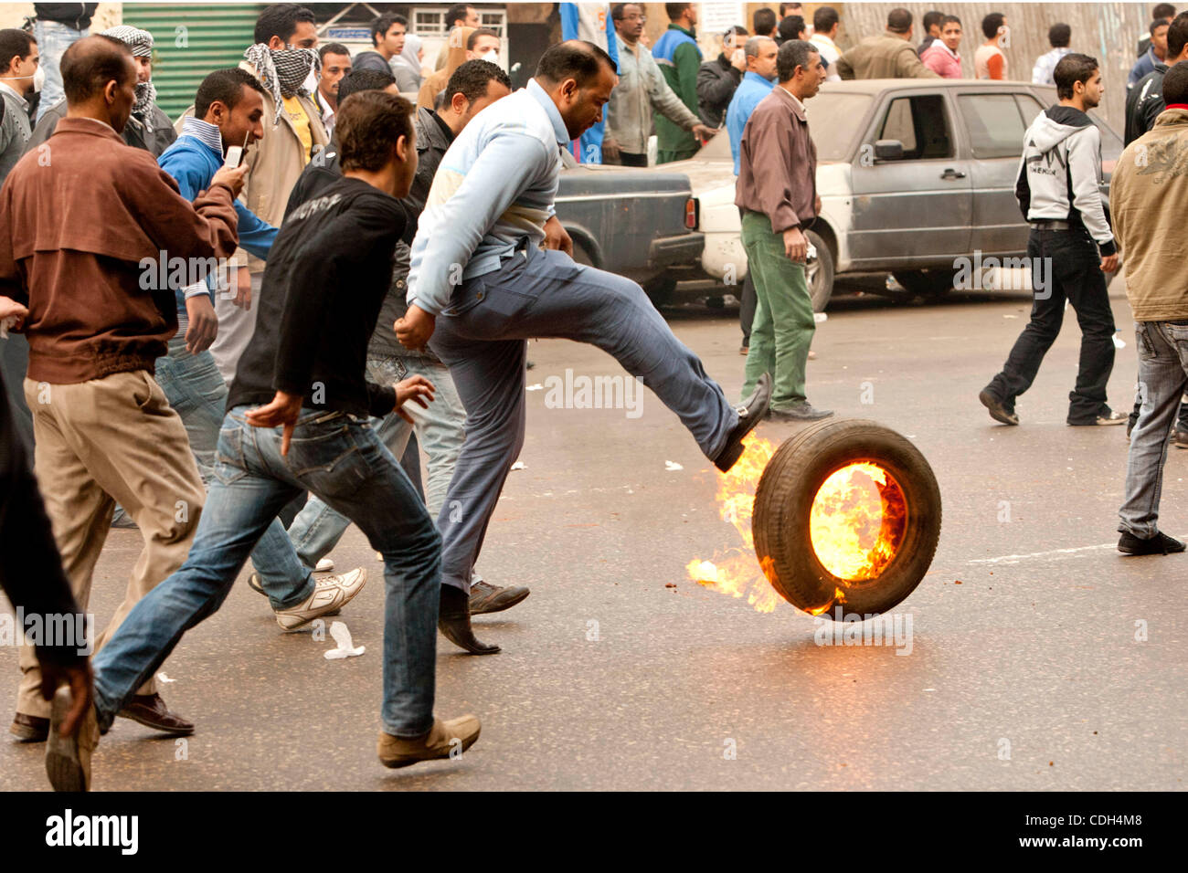 Jan 28, 2011 - Cairo, Egypt - A man kicks a burning tire. Egyptians demonstrated under the 6th October Bridge at - Stock Image