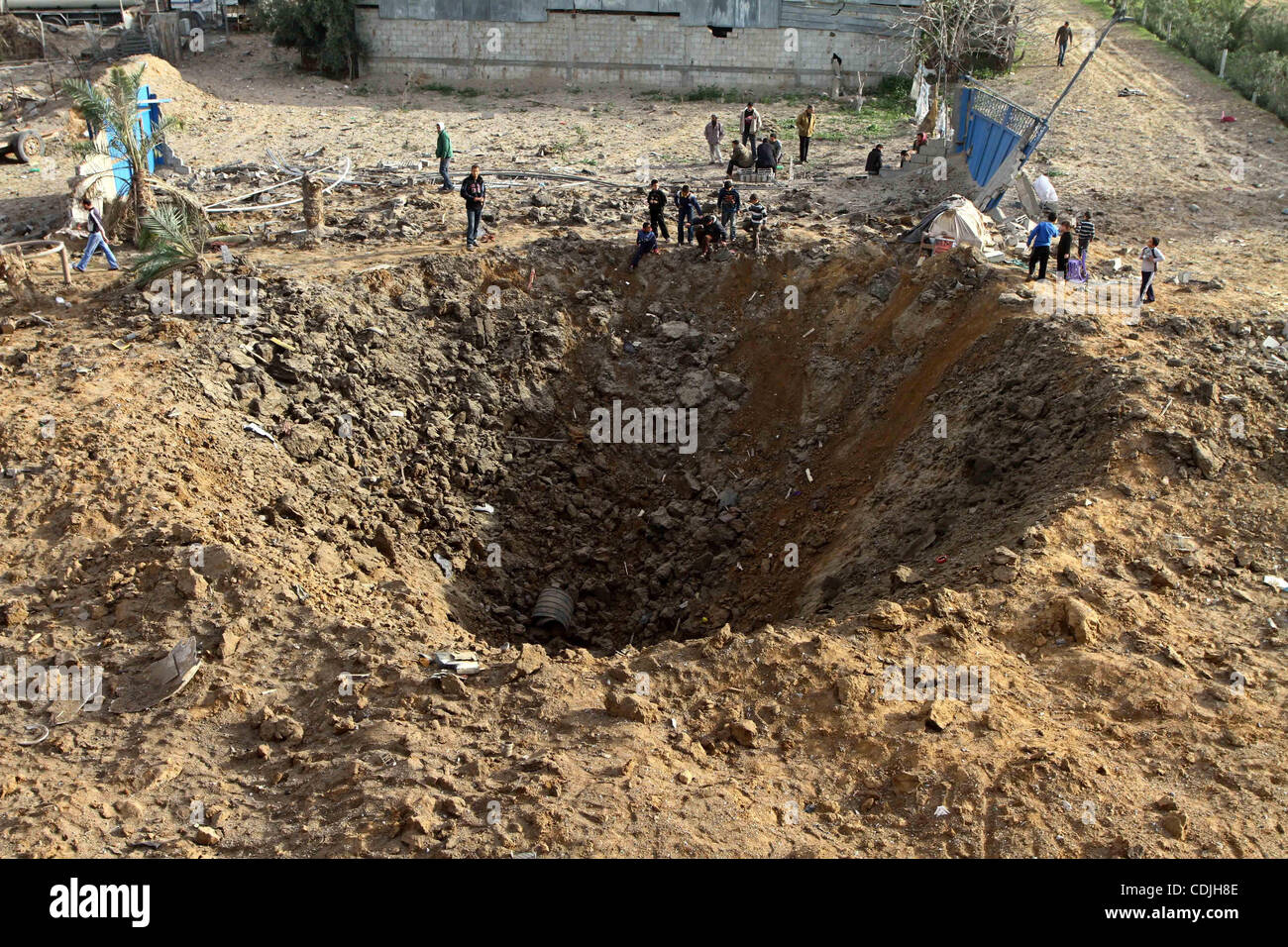 Palestinians stand next to a crater left after a missile fired from an Israeli warplane hit Nusairat refugee camp, Stock Photo