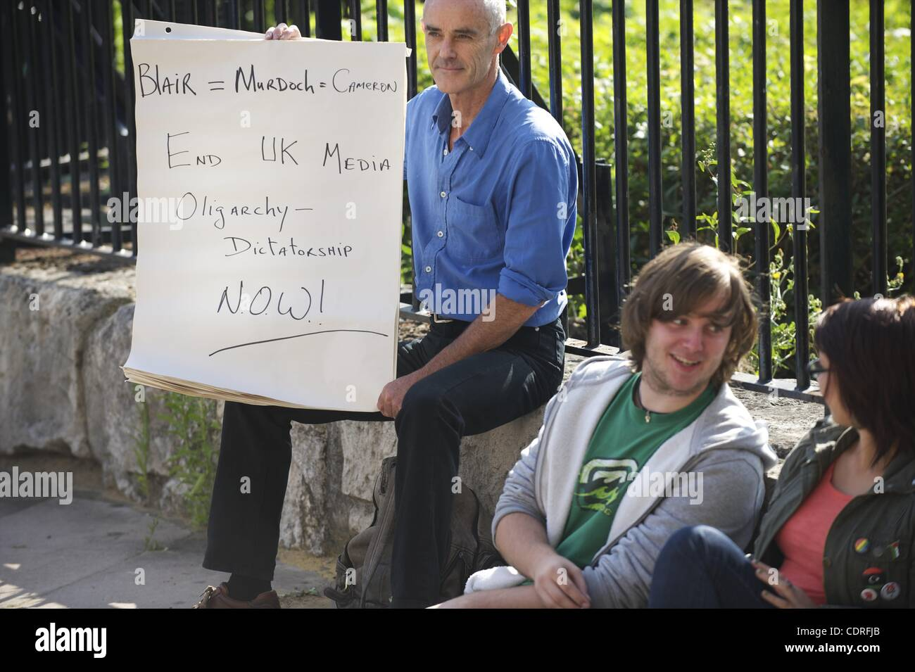 July 10, 2011 - London, England, UK - Protestors write obscenities on the final issue of the News of the World, Stock Photo