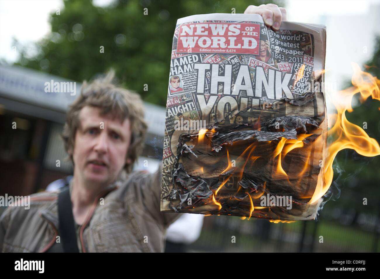 July 10, 2011 - London, England, United Kingdom - A protester burns copies of The News of the World outside News Stock Photo