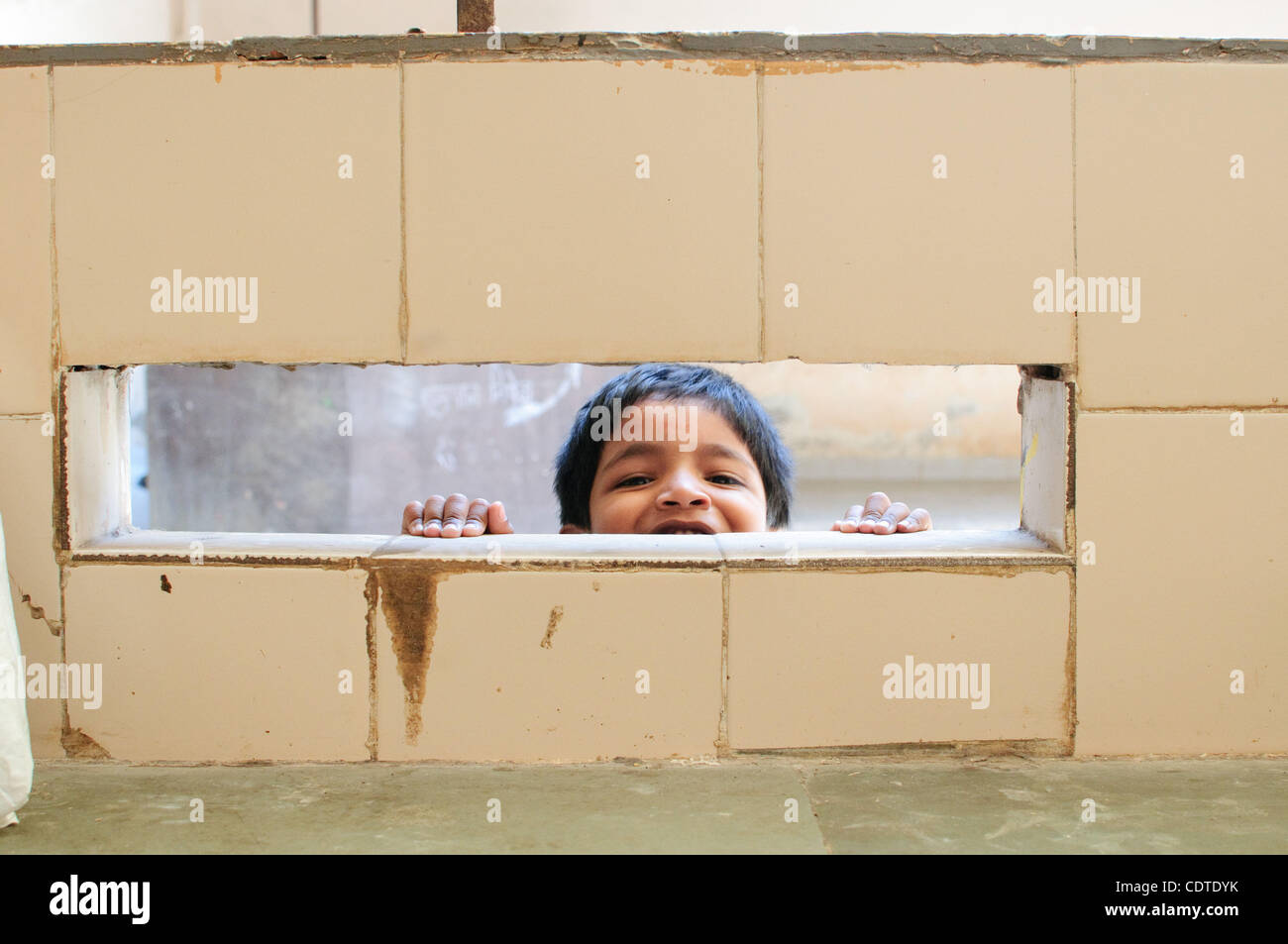 Prahul peaks out from behind the wall in a building just outside a row of stages.  In sync with India's family - Stock Image