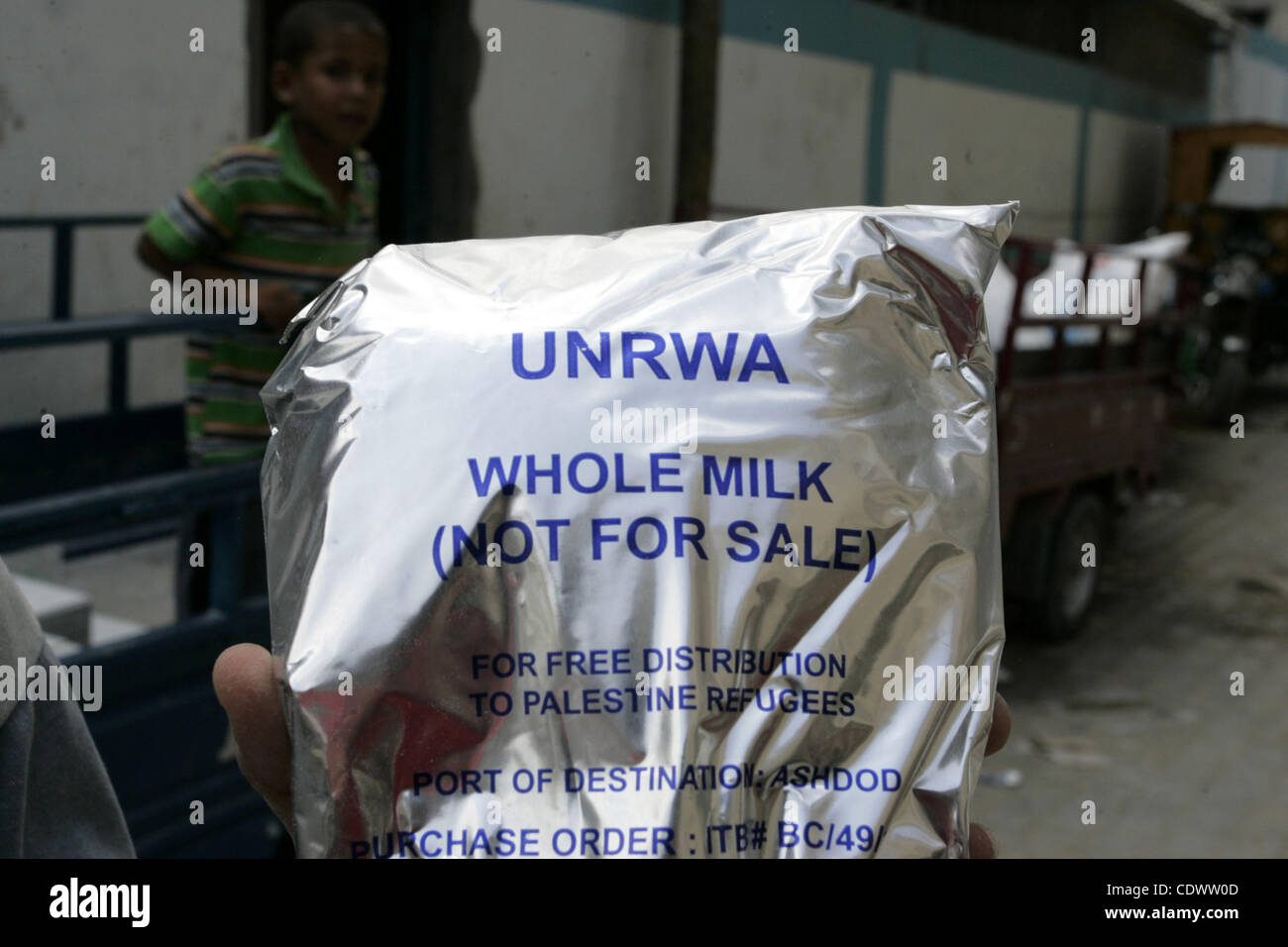 A Palestinian youth carries a bag of milk as others receive food aids from the United Nations Relief and Works Agency - Stock Image