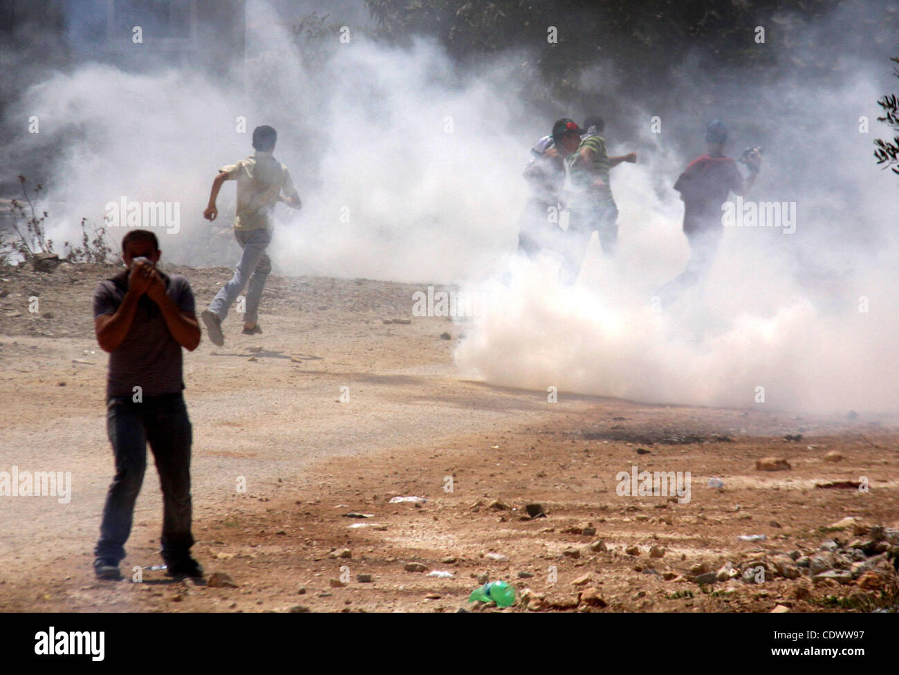 Palestinian demonstrators run as Israeli forces start to fire tear gas during clashes following a protest against - Stock Image